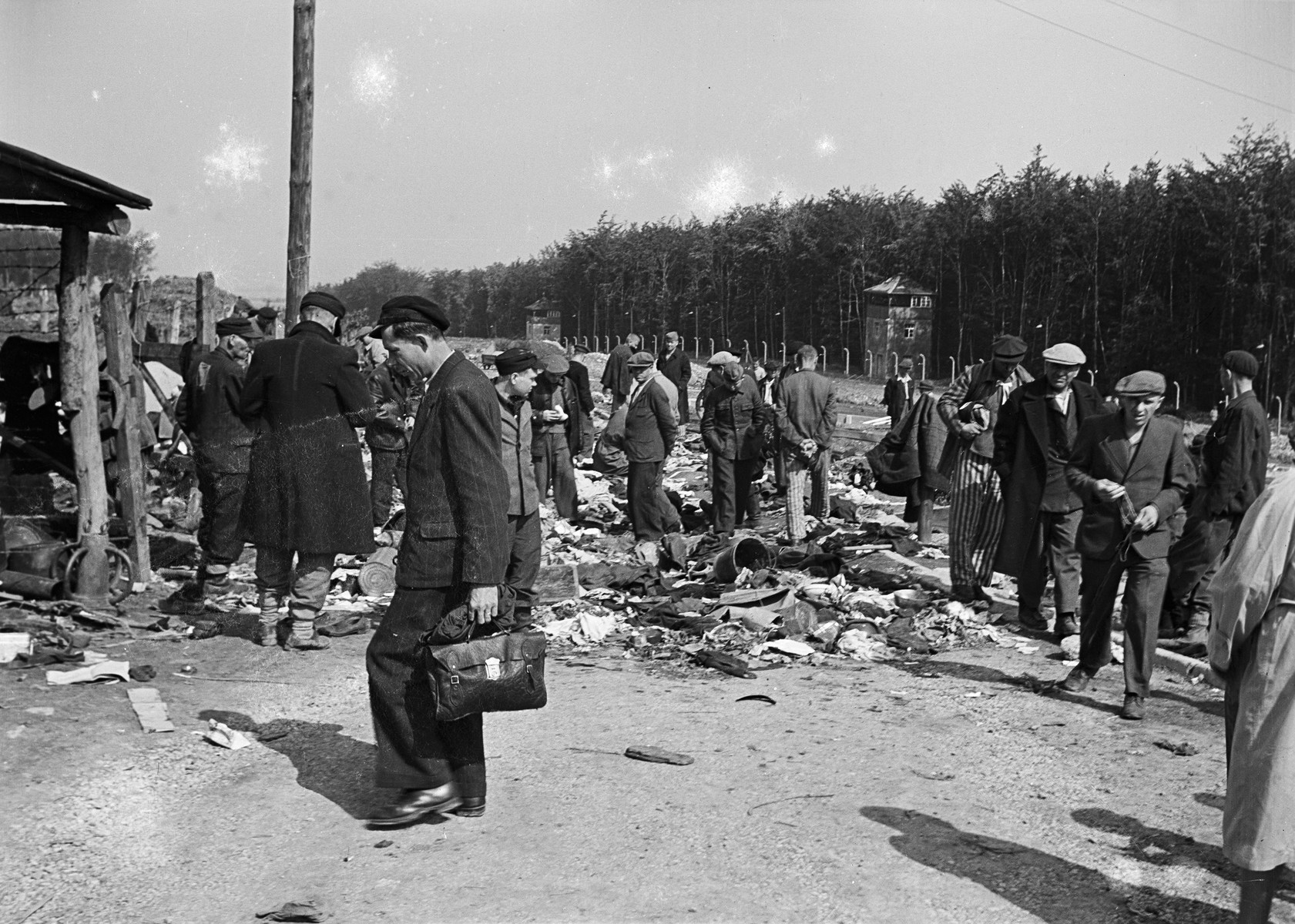 Former concentration camp inmates search through clothing and other effects after the liberation of Buchenwald.