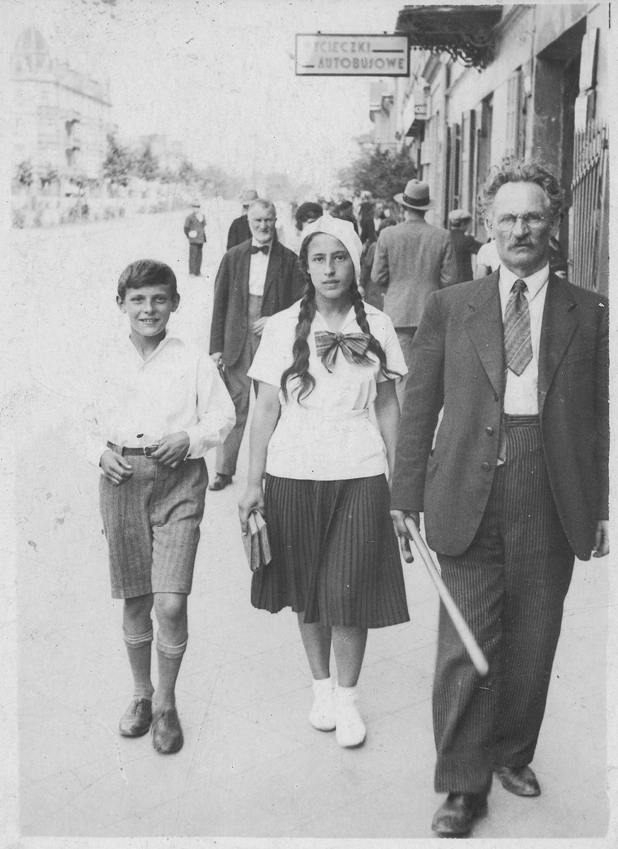 The Willenberg family walks down a street in prewar Czestochowa.   Pictured from left are Shmuel, Itta, and their father Perec.