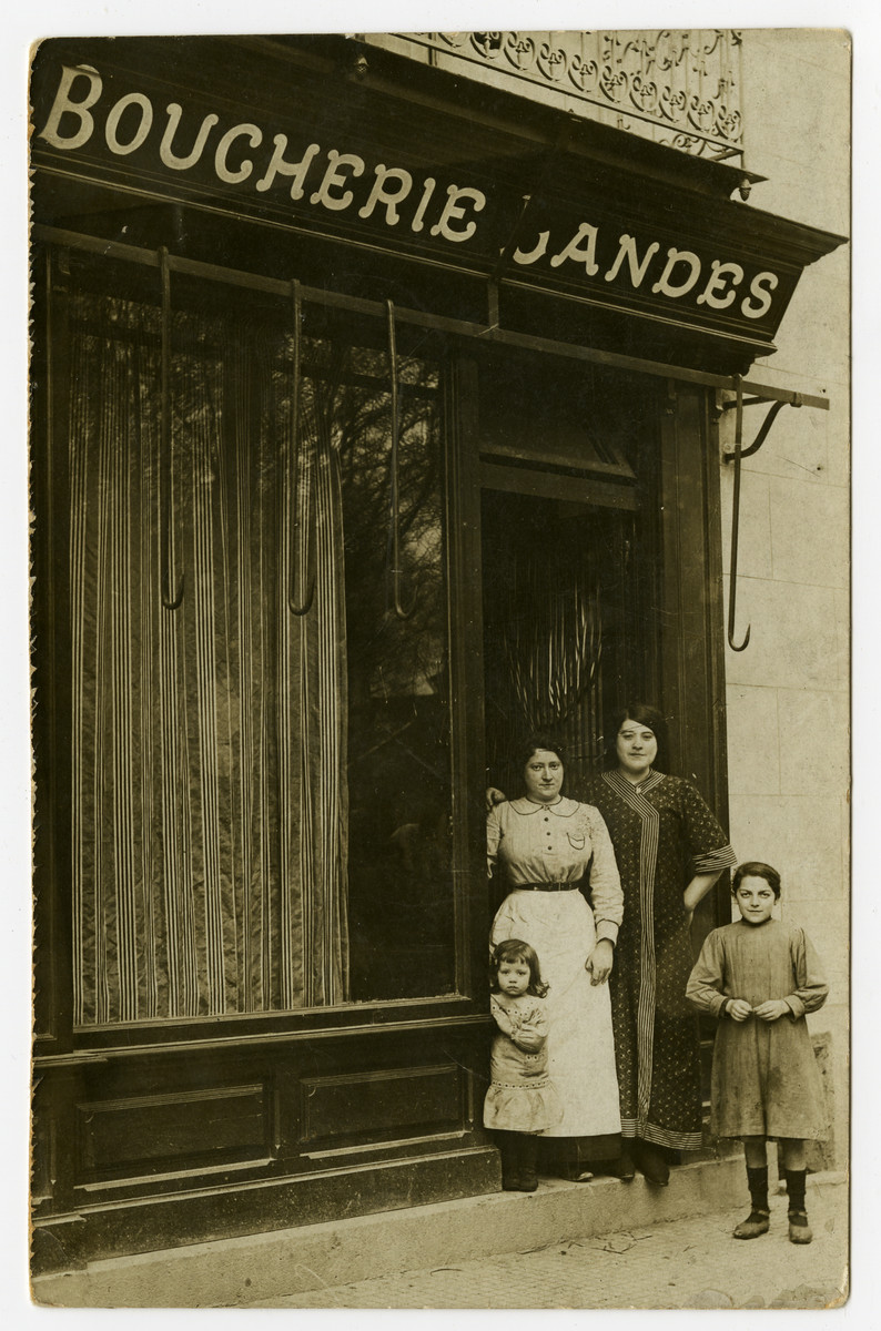 Two women and children stand outside a Boucherie in Paris.  One of the children is probably Marte (later Weber).