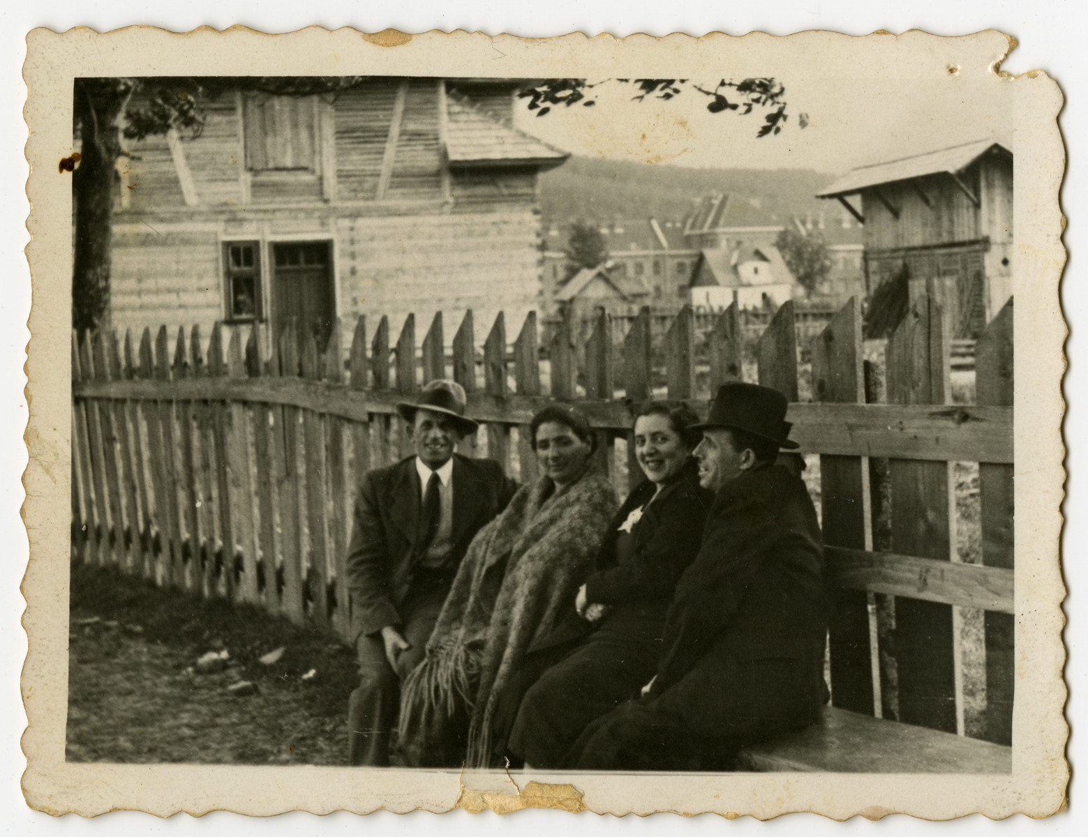 [Family and/or friends of Izak Weber sit on an outdoor bench, probably in Skole, Poland.]