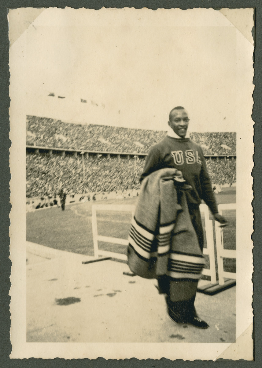 "Gold-medalist Jesse Owens carrying a blanket  while inside the Olympic stadium in Berlin.  The original caption reads: ""Jessie Owens, the fastest man in the world."""