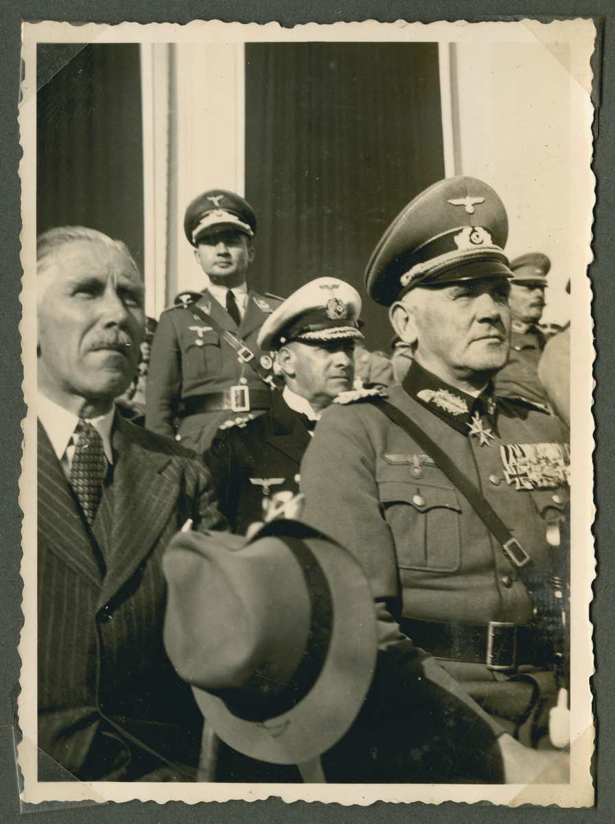 Nazi officials stand at attention during a Reichsparteitag rally.  In front are Franz von Papen and General von Blomberg; behind them is Admiral Erich Raeder.