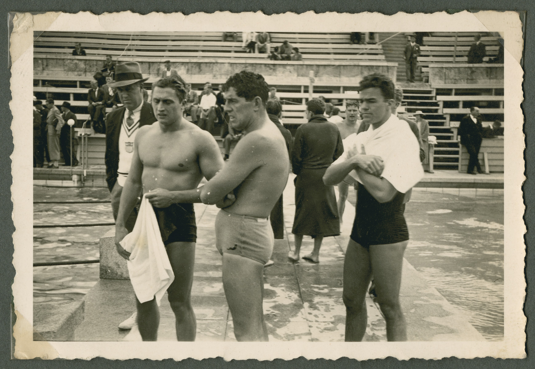 American swimmers stand by the side of the pool either before or after a competition.  Pictured are Peter Fick and Jack Medica.