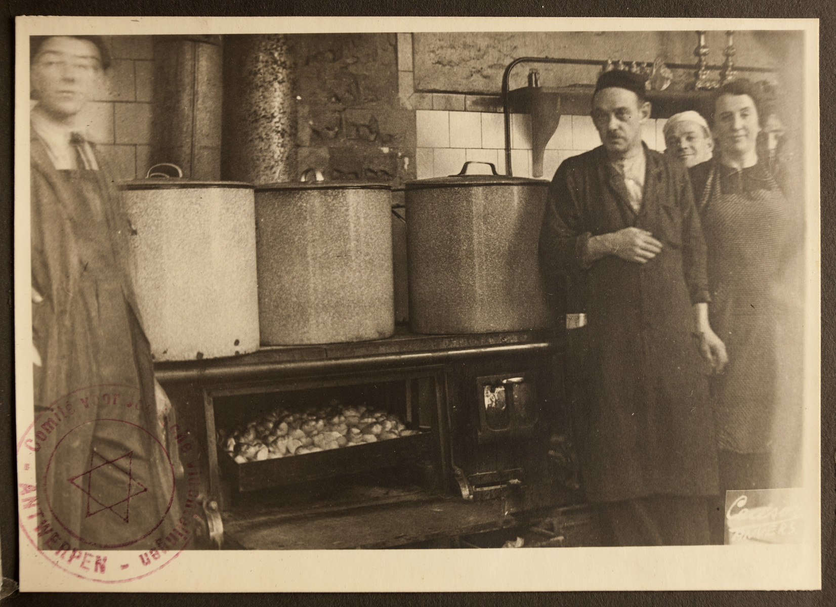 The kitchen staff of the Jewish Refugee Aid Committee of Antwerp stands by three large pots.