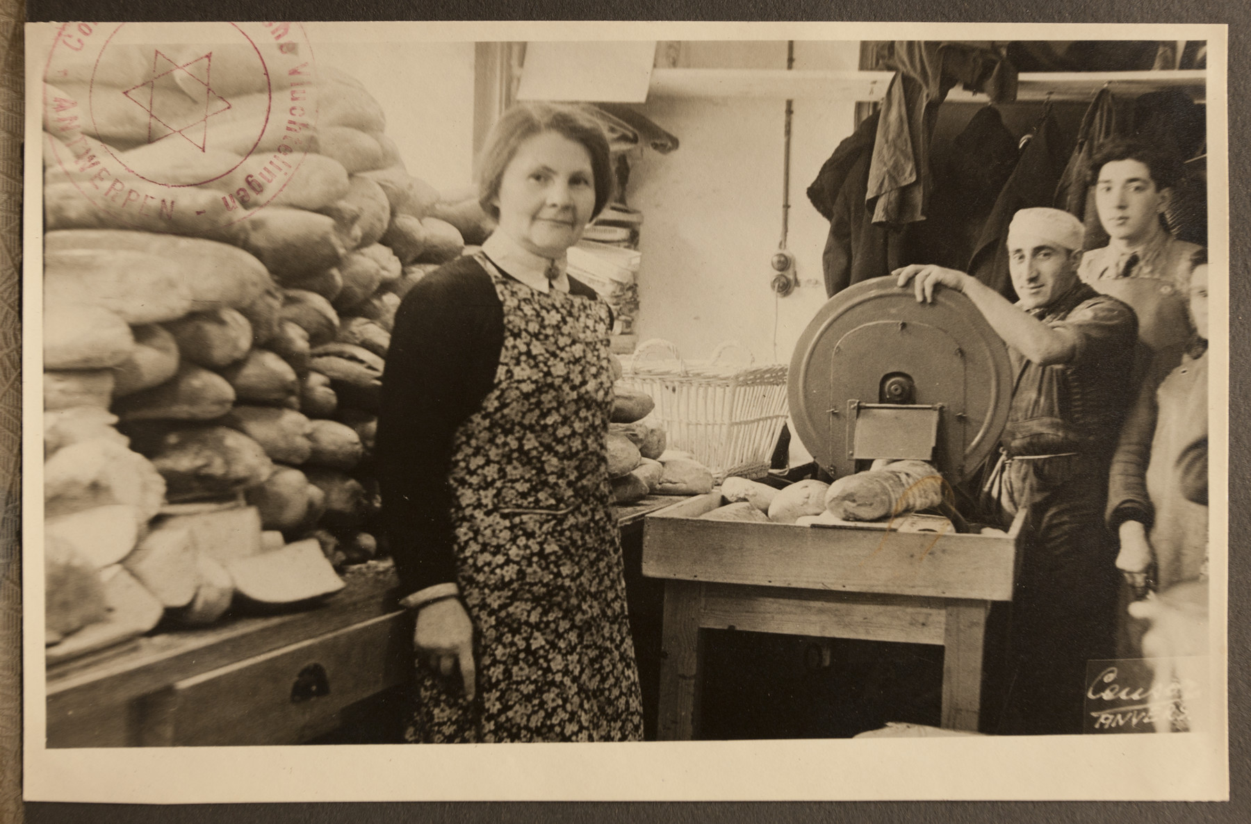 Kitchen workers of the Jewish Refugee Aid Committee of Antwerp slice large loaves of bread.