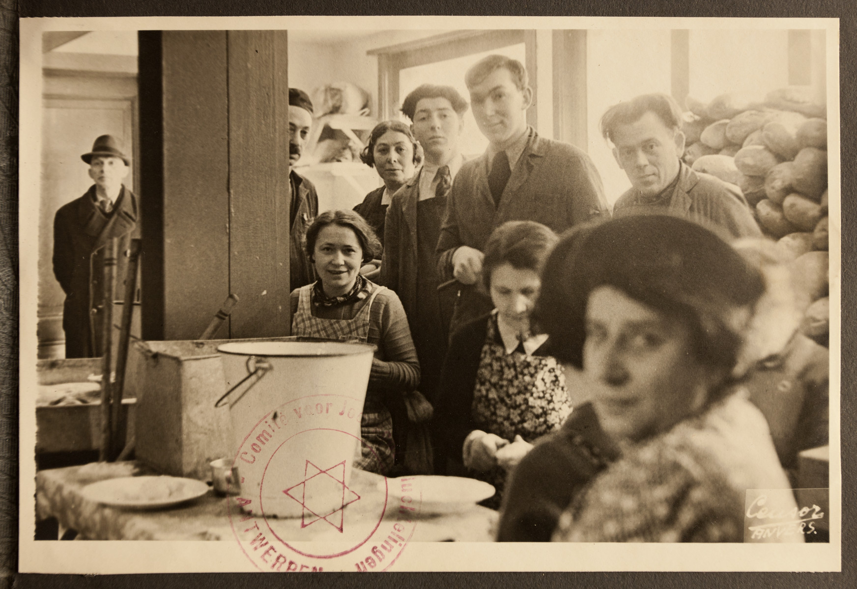 Men and women gather in the kitchen of the Jewish Refugee Aid Committee of Antwerp.