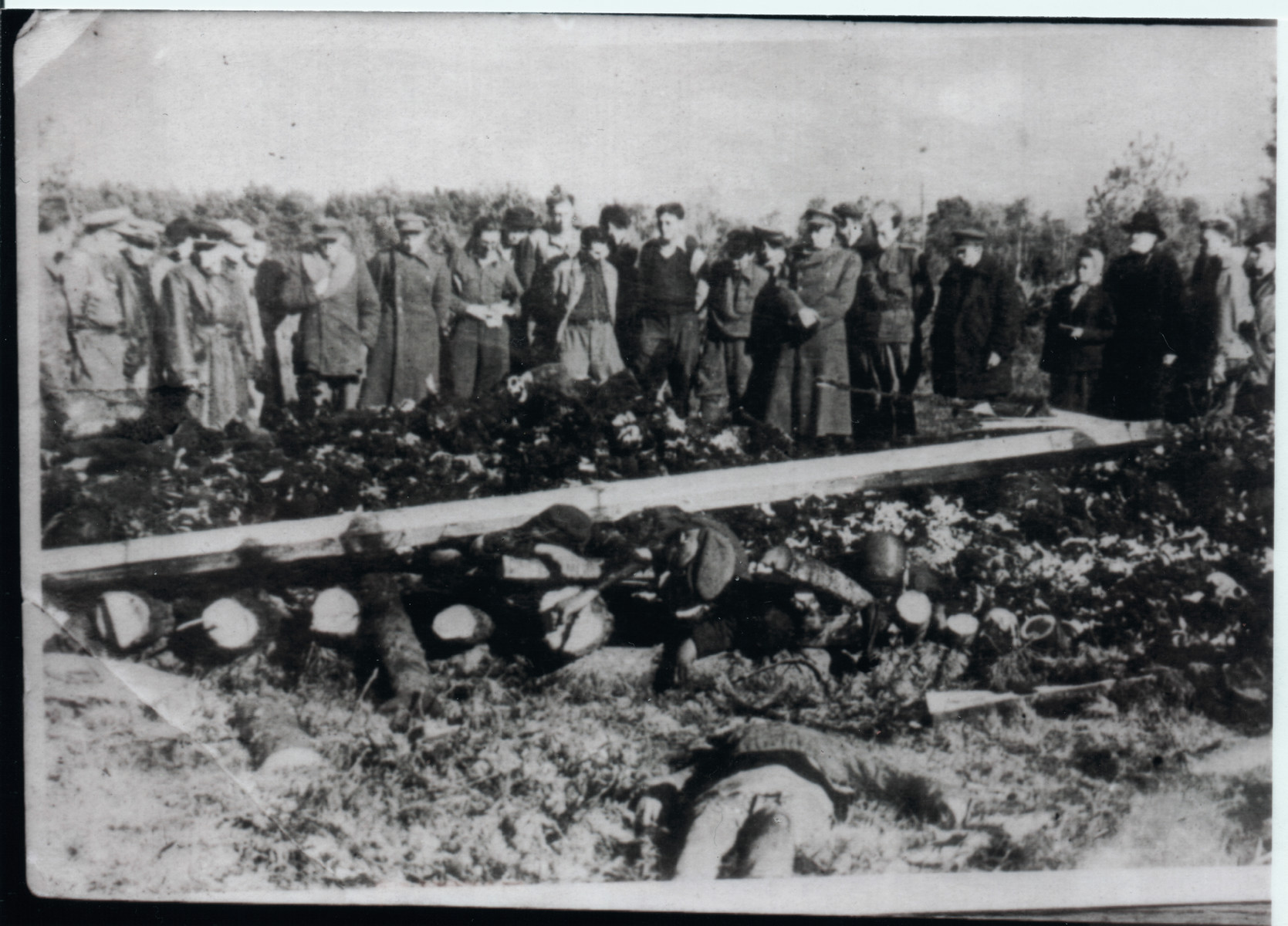 A group of survivors stares at the remains of other charred prisoners in Klooga following liberation.