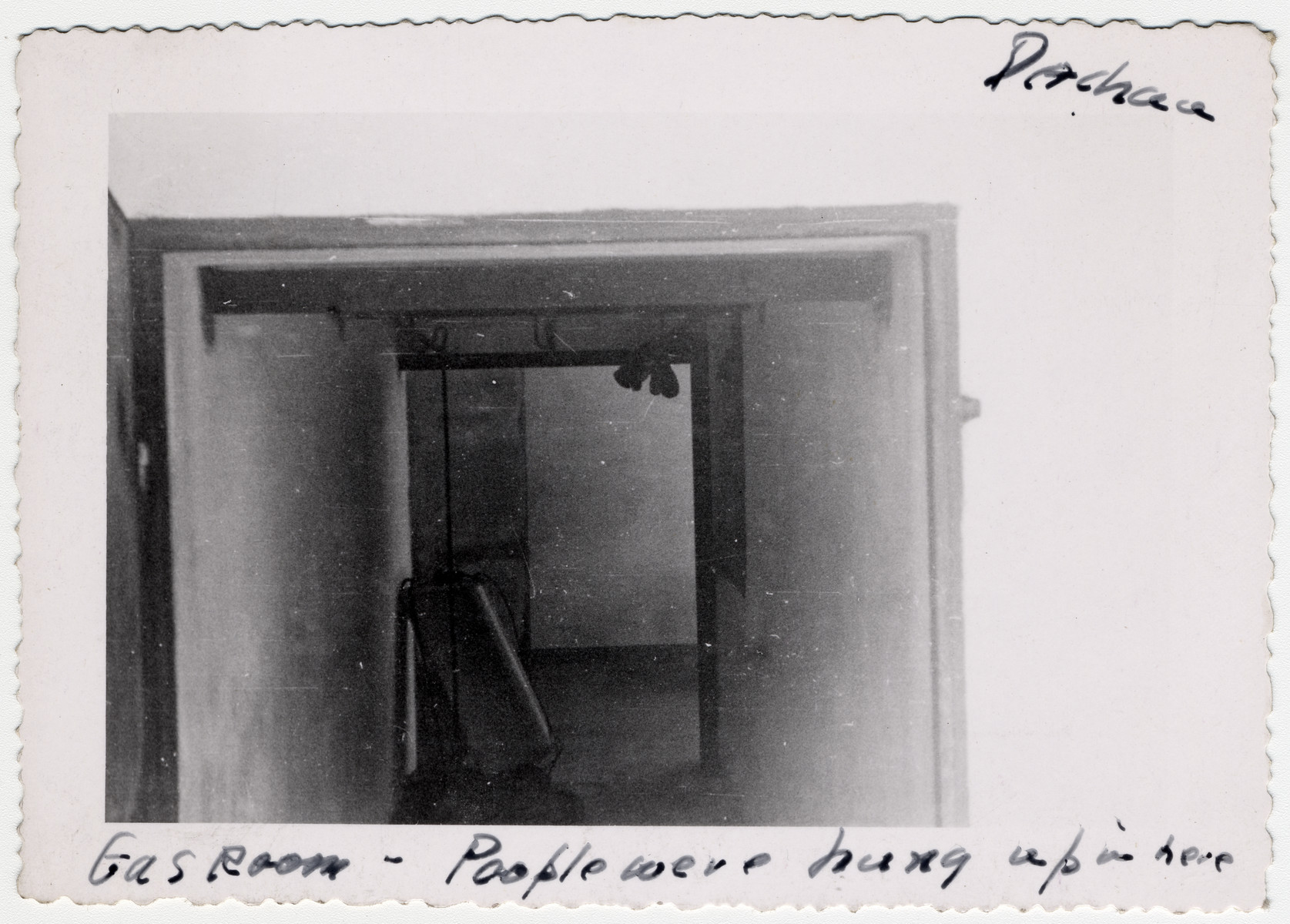 """Interior view of a gas chamber in the Dachau concentration camp after liberation.  The original caption reads: """"Gas room -- People were hung up in here."""""""