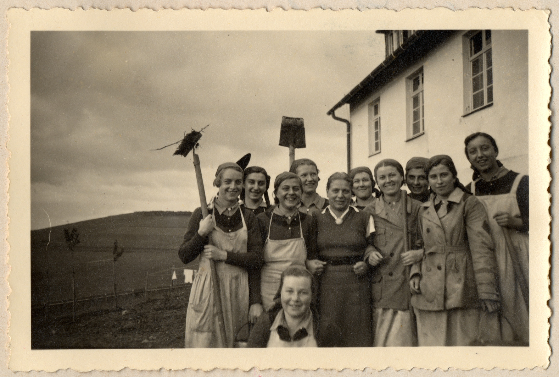 Young German women in the Reich Labor Service are photographed with agricultural tools on the estate where they are working.