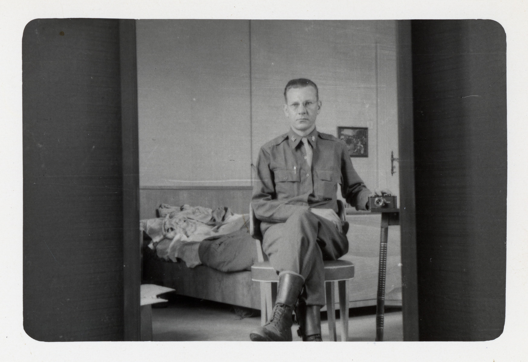 Lt. Colonel George Raymond Snyder poses in his quarters with his hand on a camera.