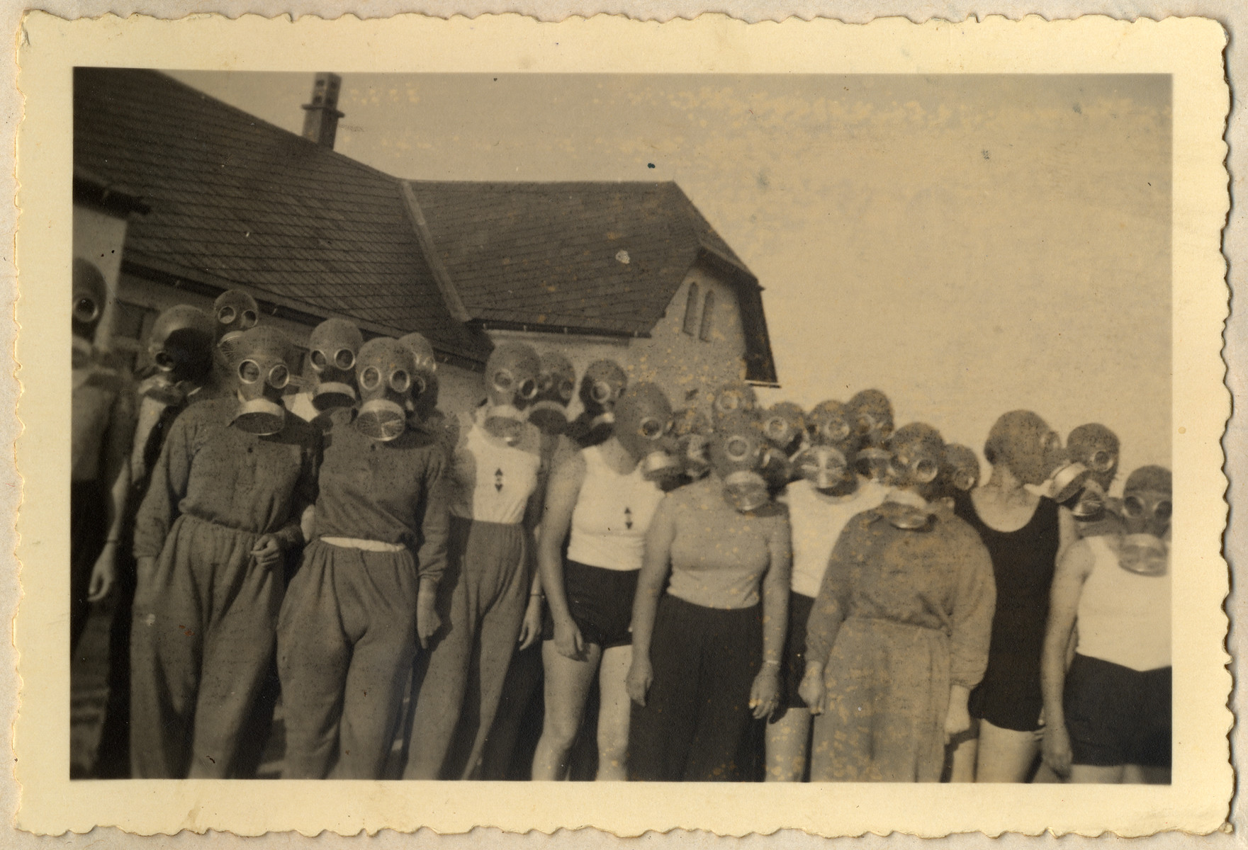 Young German women in the Reich Labor Service are photographed wearing gasmasks during an air raid drill (some wear BdM shirts).