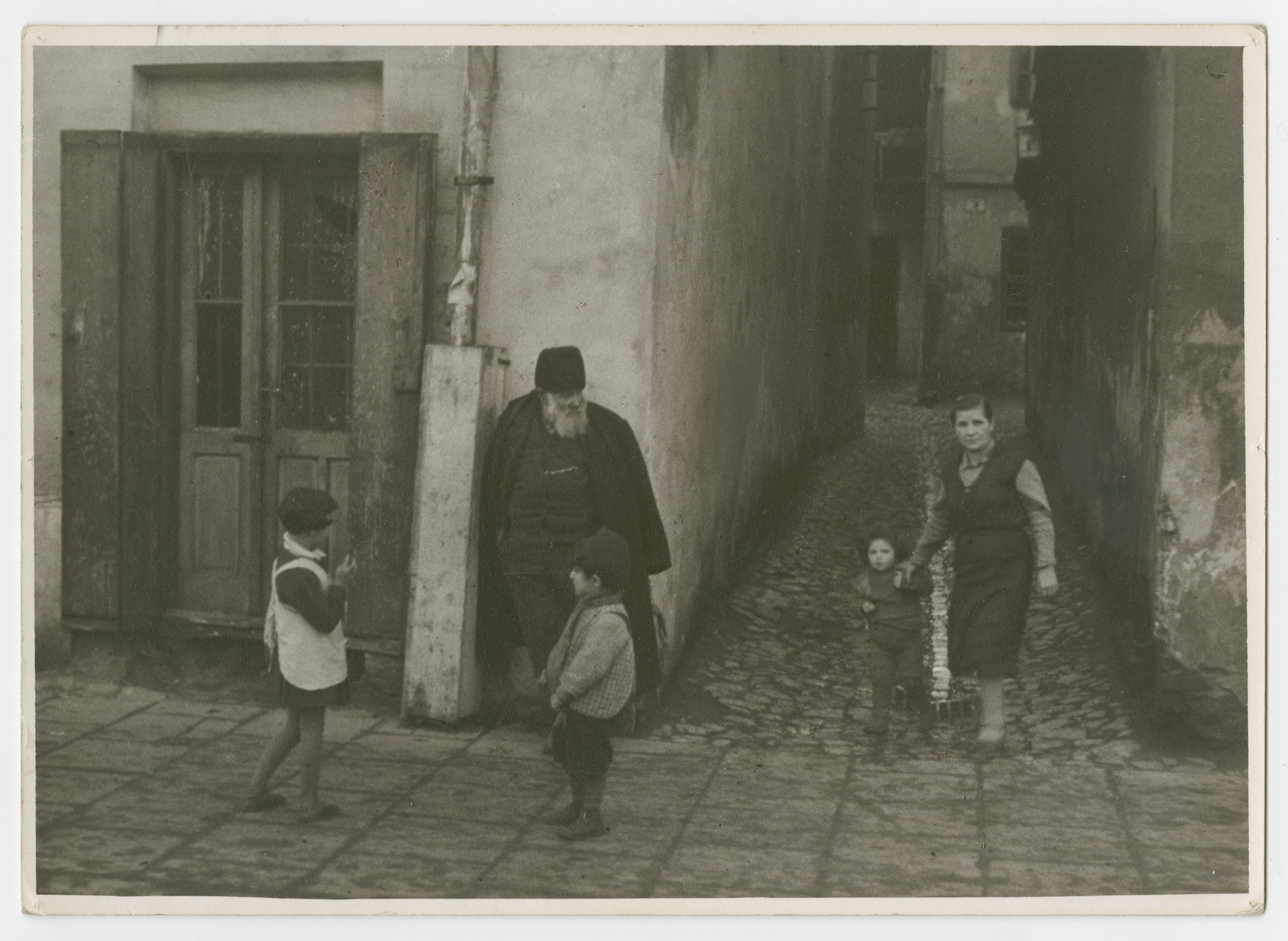 """A religious Jew leans against a building while a woman and children walk and play nearby.  Photograph is used on page 137 of Robert Gessner's """"Some of My Best Friends are Jews.""""  [He is probably the caretaker of a yeshiva.]"""