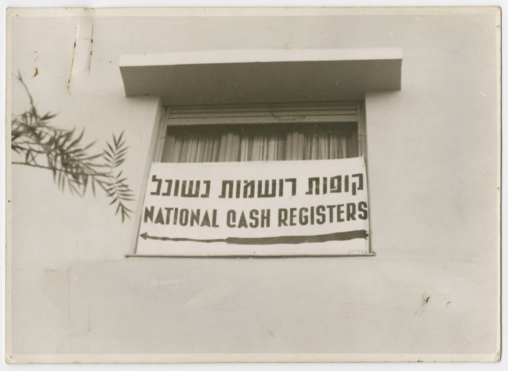 """A sign in a window points to the location of the National Cash Registers [probably in Tel Aviv].  Photograph is used on page 179 of Robert Gessner's """"Some of My Best Friends are Jews."""" The typed caption on the back of the photograph reads, """"American tills for Jewish businesses."""""""