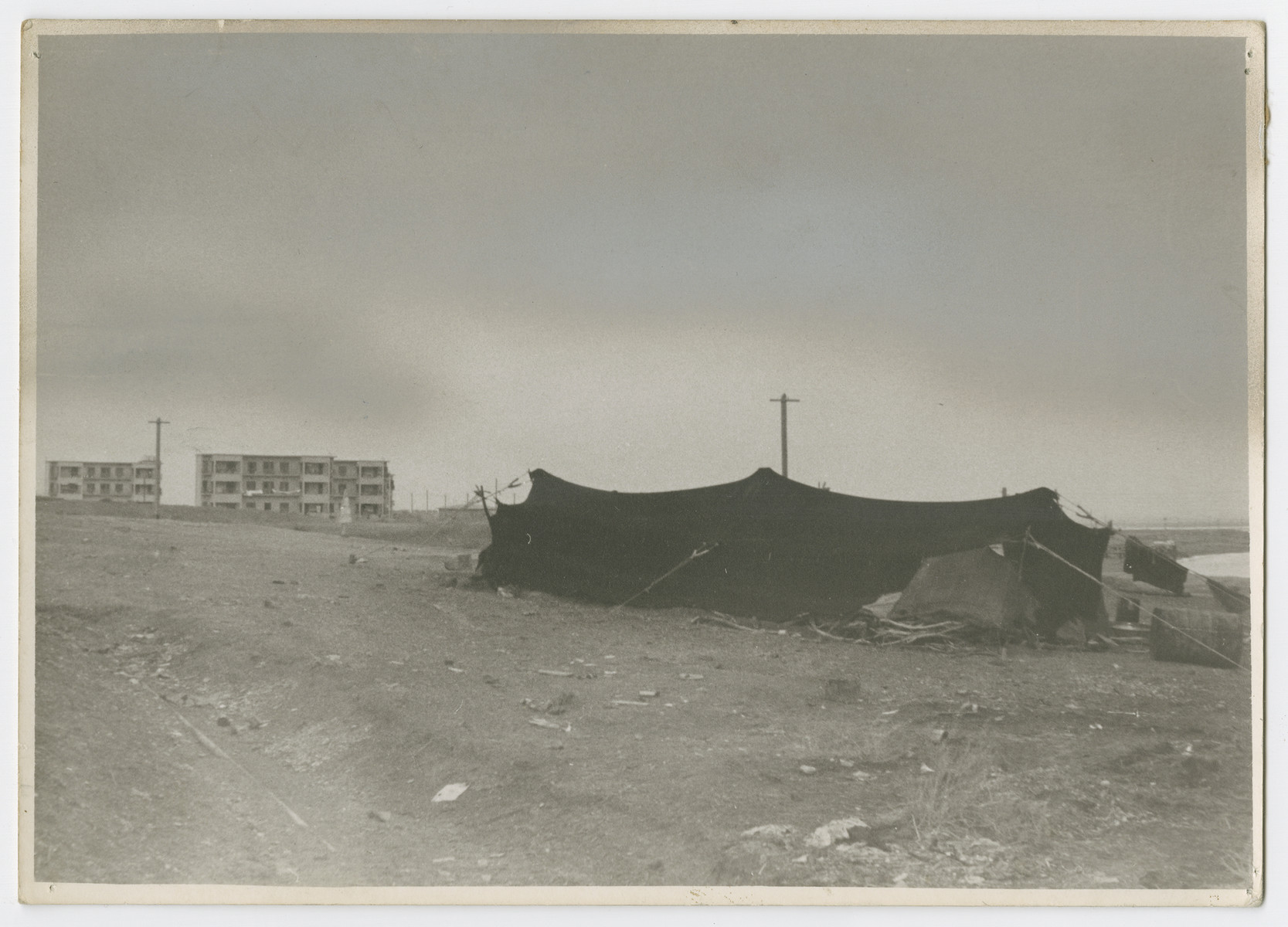 "View of a Bedouin tent and a Jewish housing project near the banks of the Dead Sea.   Photograph is used on page 188 of Robert Gessner's ""Some of My Best Friends are Jews."" The pencil inscription on the back of the photograph reads, ""Dead Sea with PJ and Arb workers."""