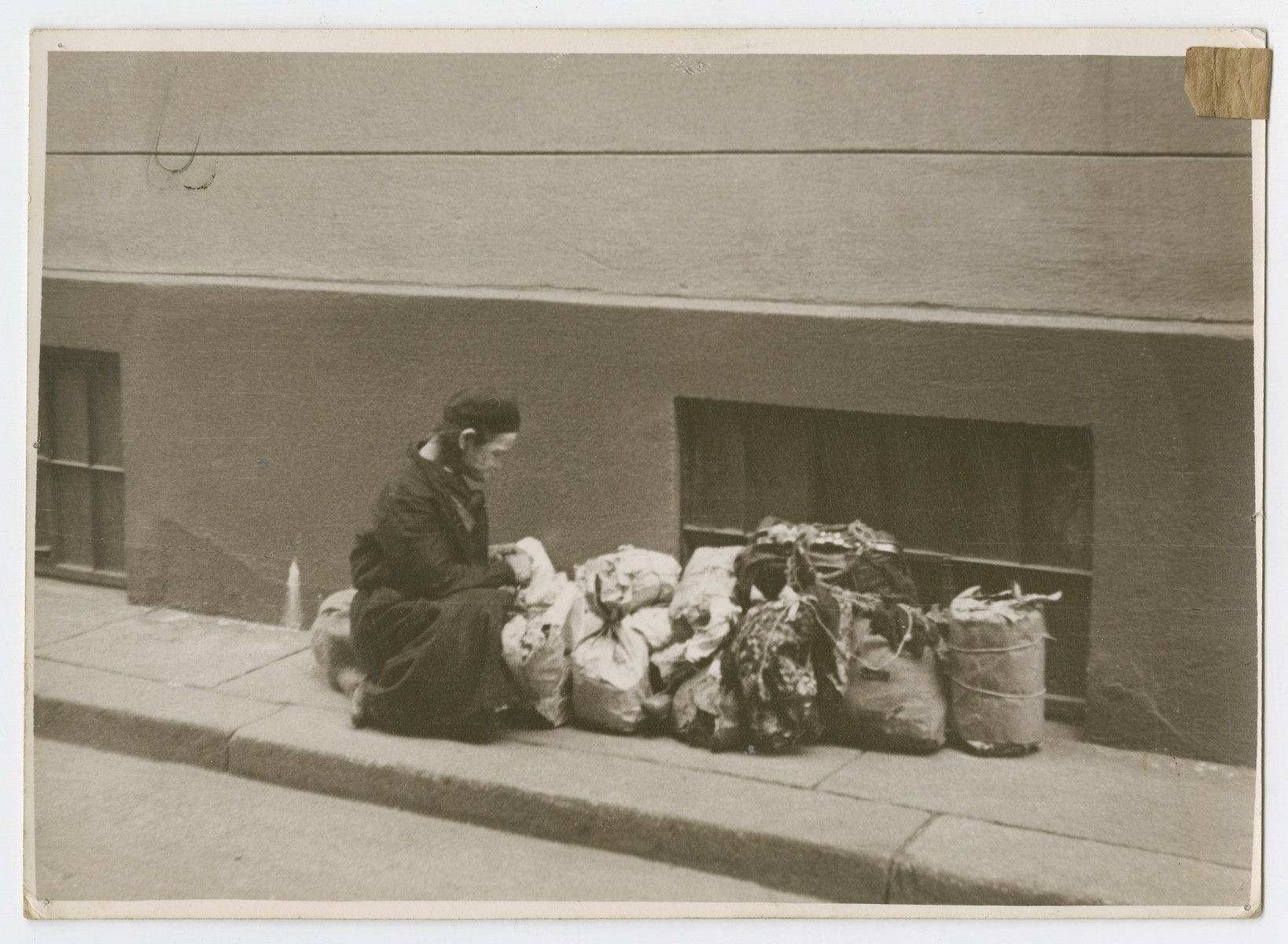 "A religious Jews [probably in Poland] kneels on a sidewalk next to bags of trash,  Photograph is used on page 90 of Robert Gessner's ""Some of My Best Friends are Jews."""