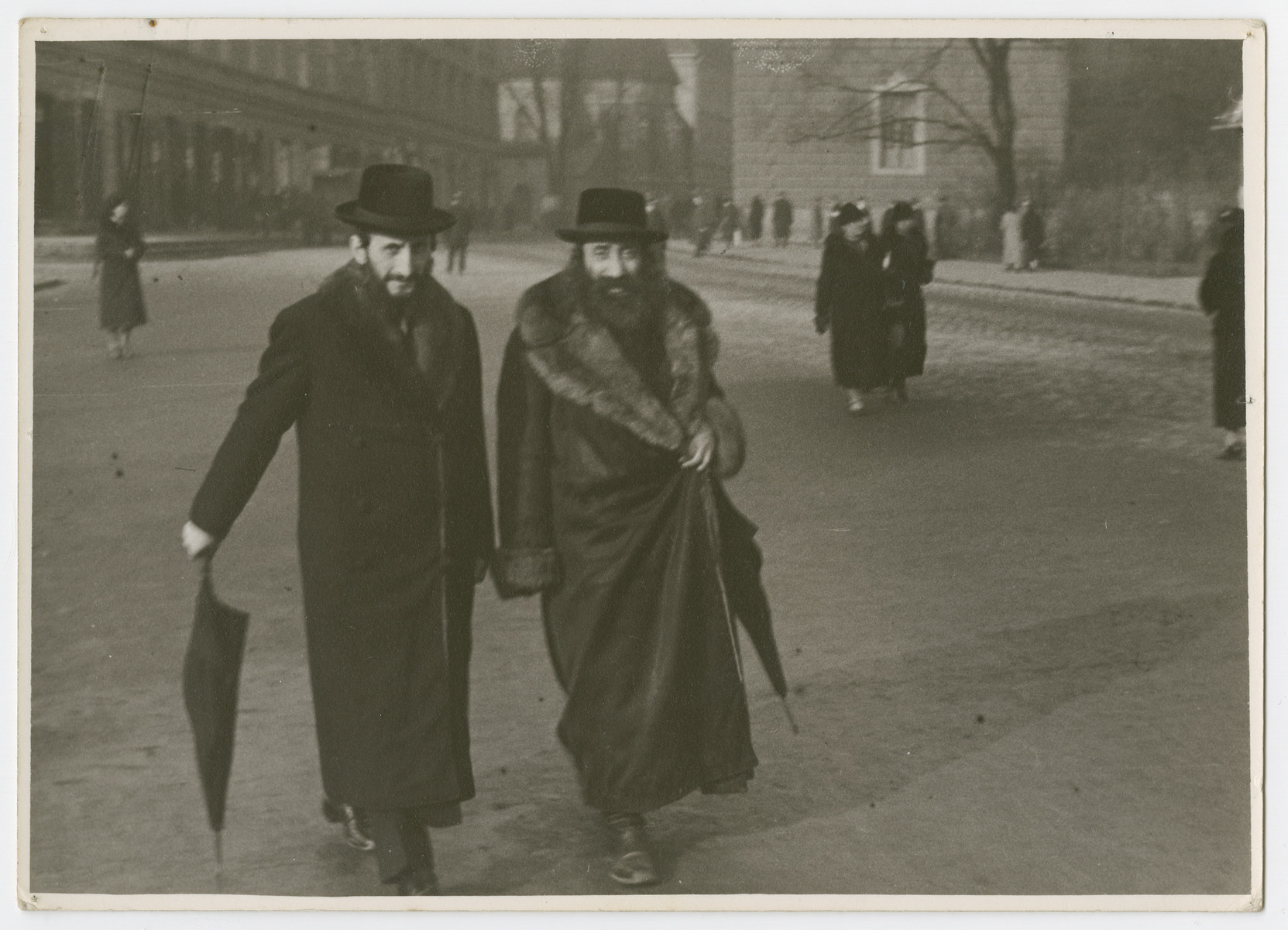 """A rabbi and his disciple walk down a street in Poland.  Photograph is used on page 119 of Robert Gessner's """"Some of My Best Friends are Jews."""" The pencil inscription on the back of the photograph reads, """"Head Rabbi."""""""