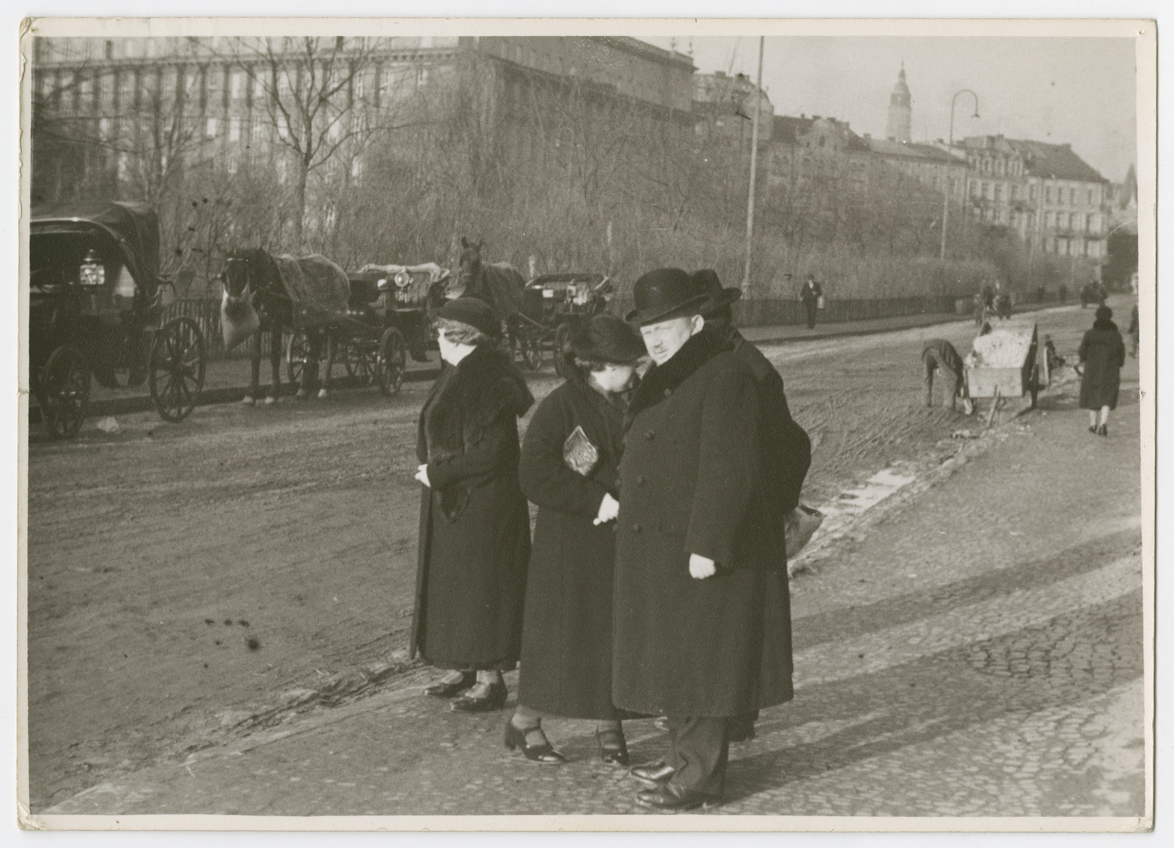 "A man and two women stand on a sidewalk [probably in Krakow].  Photograph is used on page 135 of Robert Gessner's ""Some of My Best Friends are Jews."""