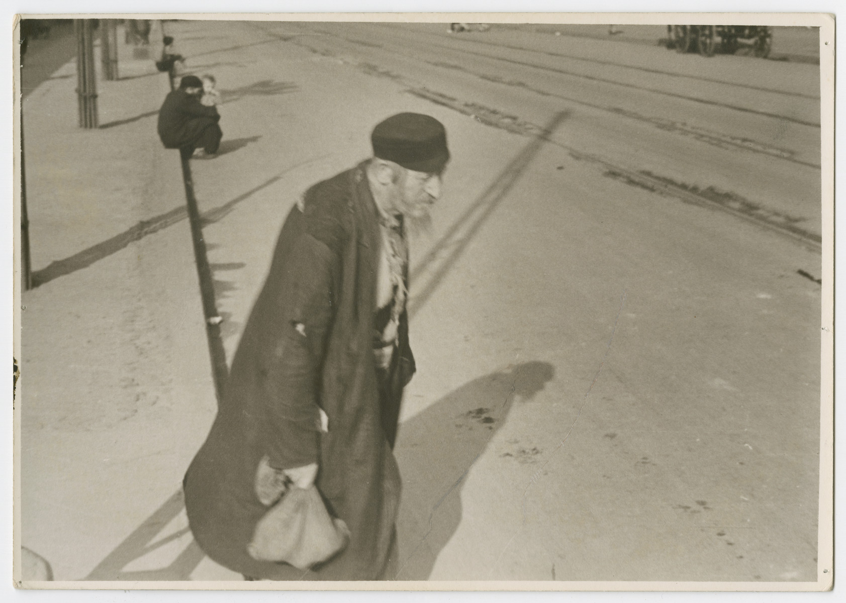 "An impoverished Jewish man walks down a street in Poland.  Photograph is used on page 125 of Robert Gessner's ""Some of My Best Friends are Jews."" The pencil inscription on the back of the photograph reads, ""Beggar."""