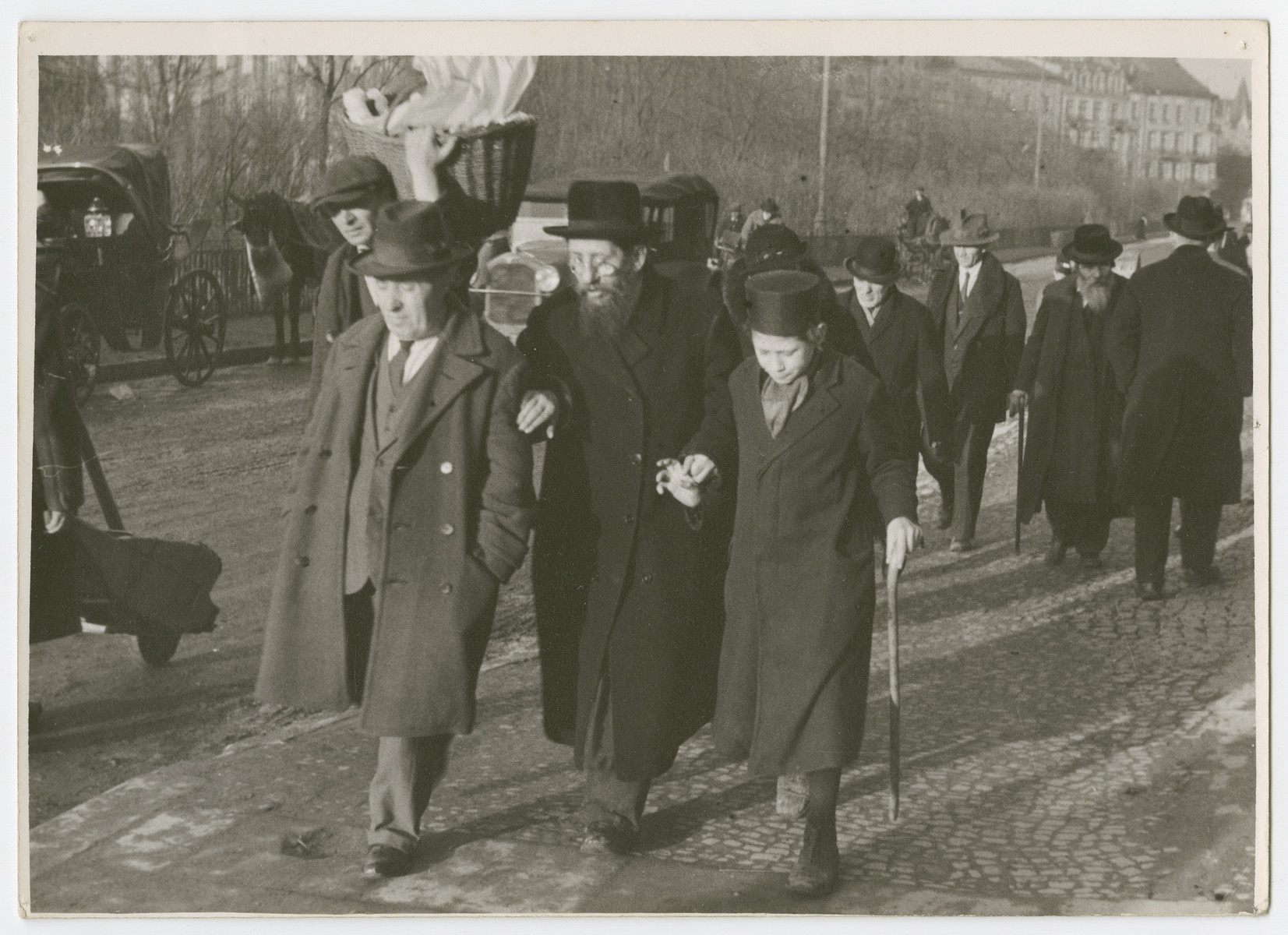 "A group of religious Jews walk down a street in Karkow.  Photograph is used on page 139 of Robert Gessner's ""Some of My Best Friends are Jews."""