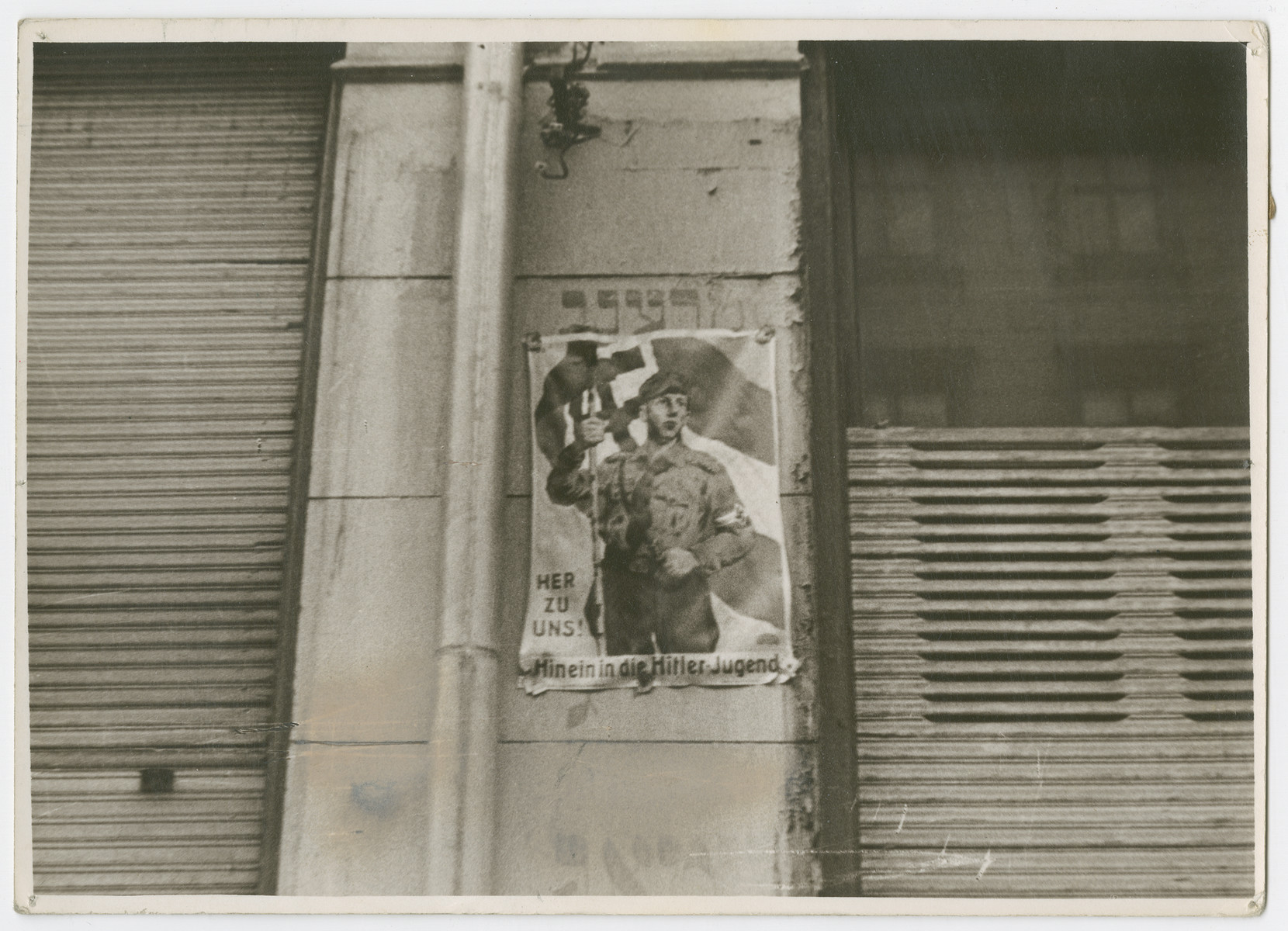 "A poster recruiting for the Hitler Youth is plastered over a formerly Jewish building. The old Yiddish inscriptions can be seen behind the poster.  Photograph is used on page 64 of Robert Gessner's ""Some of My Best Friends are Jews. "" The pencil inscription on the back of the phograph reads, ""Germany."""