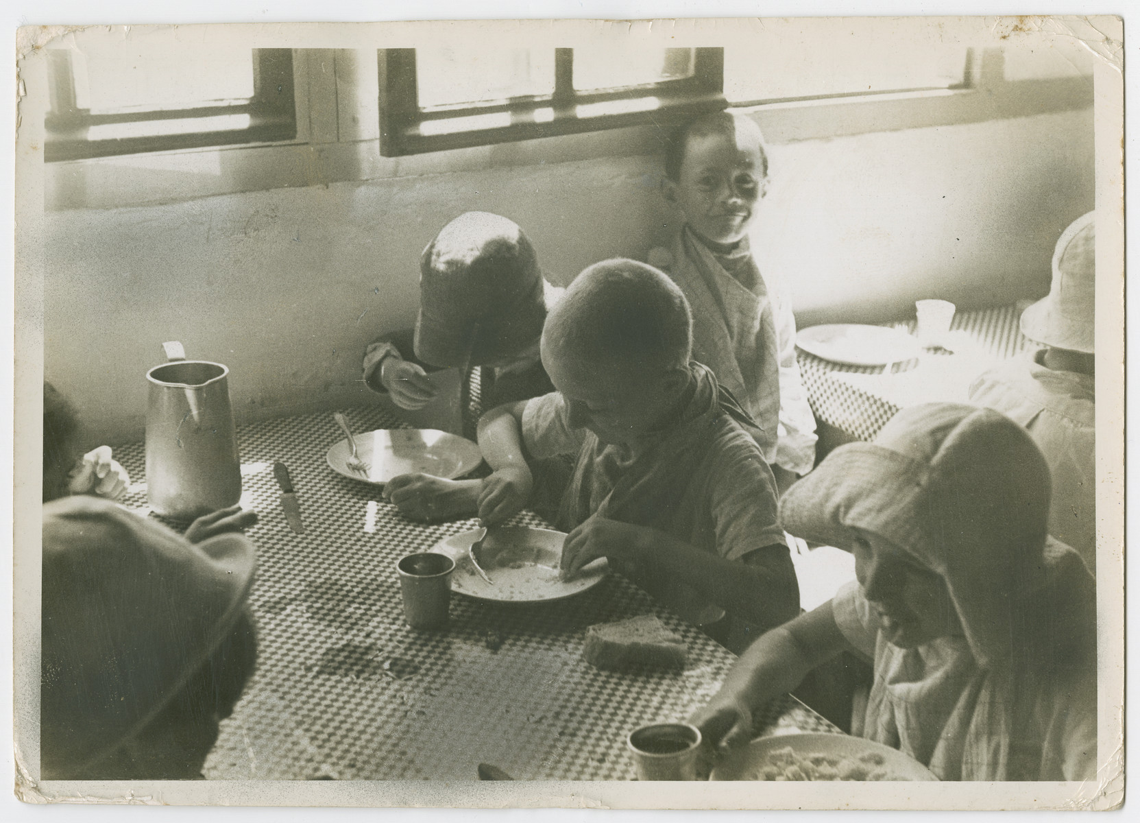 """German Jewish refugee children eat a meal in a children's home in France.    Photograph is used on page 34 of Robert Gessner's """"Some of My Best Friends are Jews.""""  The pencil inscription on the back of the photograph reads, """"France."""""""