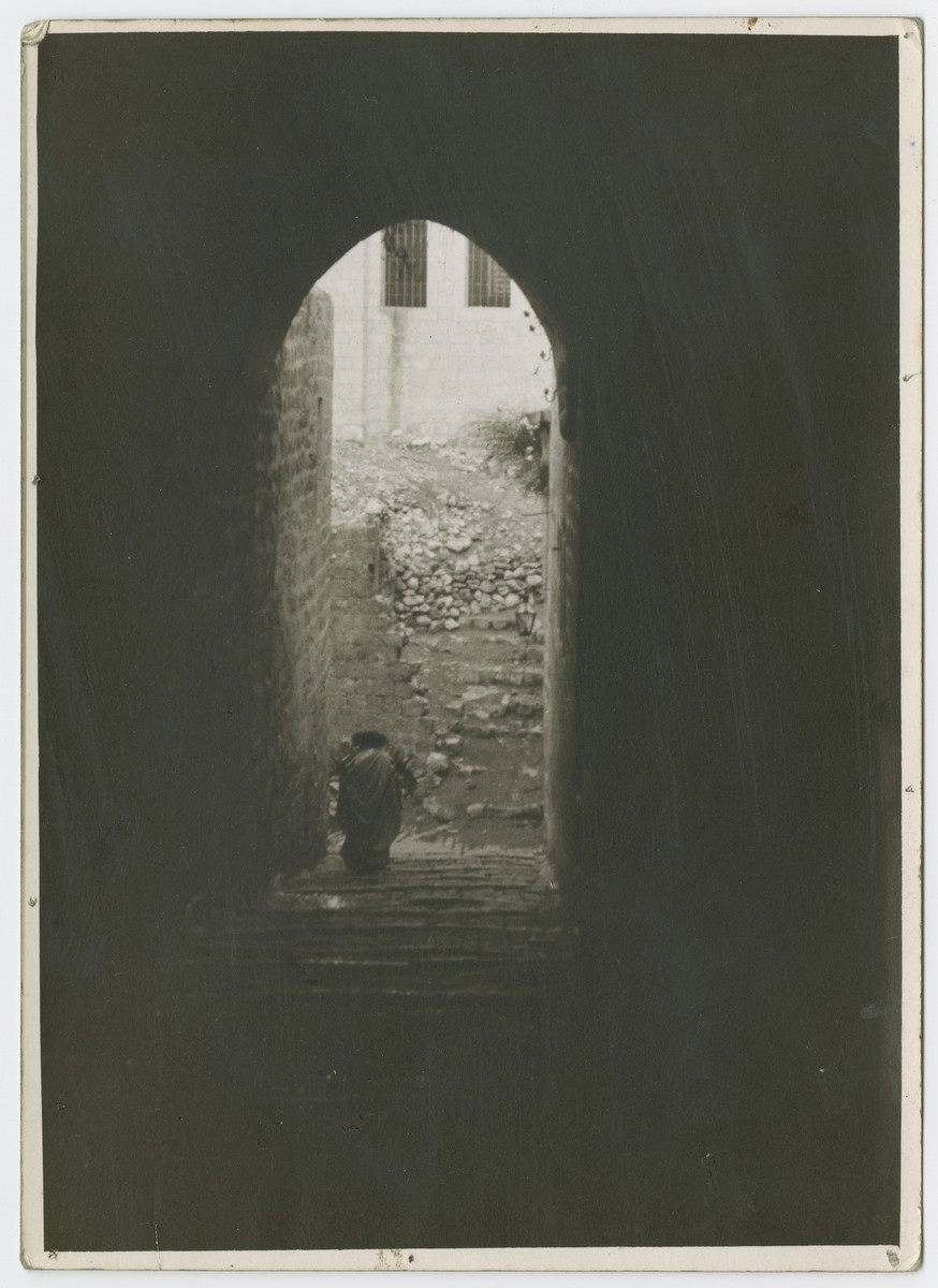 """View of a religious Jews walking through an archway and down a flight of steps [possibly in Jerusalem].  Photograph is used on the title page of Robert Gessner's """"Some of My Best Friends are Jews."""""""
