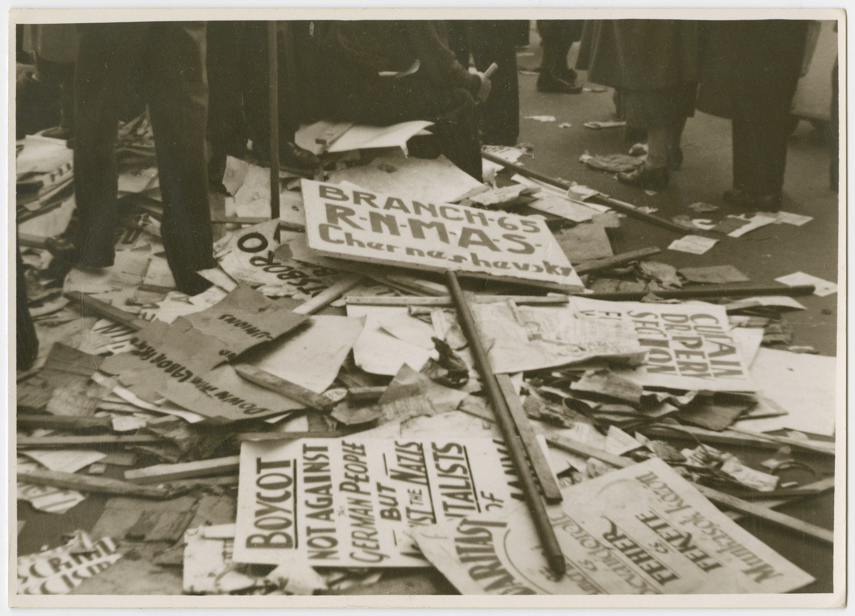 A pile of protest signs about an anti-Nazi boycott lie on the ground.