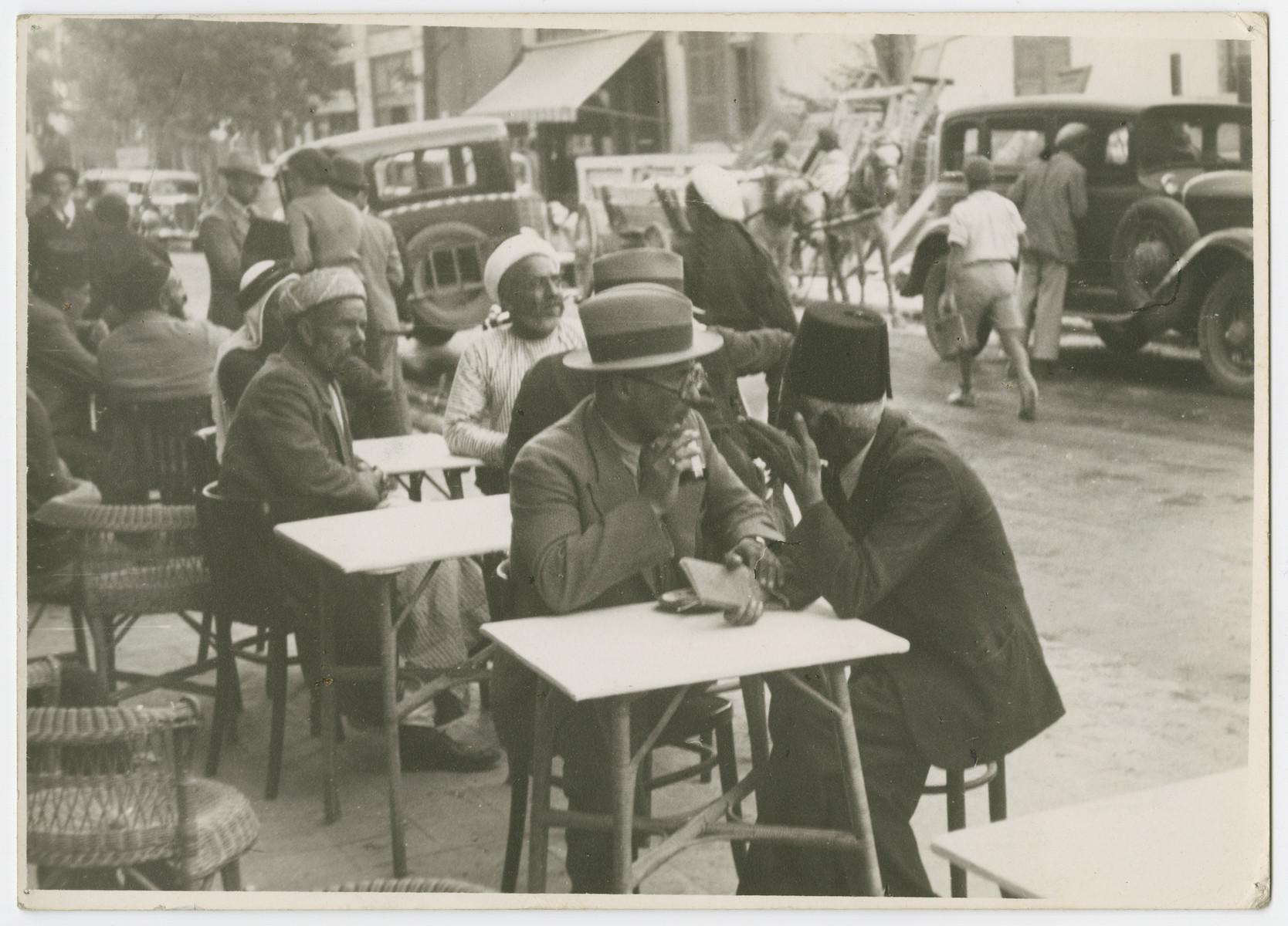 "Men sit at sidewalk cafes in Tel Aviv and negotiate land purchases.  Photograph is used on page 182 of Robert Gessner's ""Some of My Best Friends are Jews."" The pencil inscription on the back of the photograph reads, ""Bartering for land."""