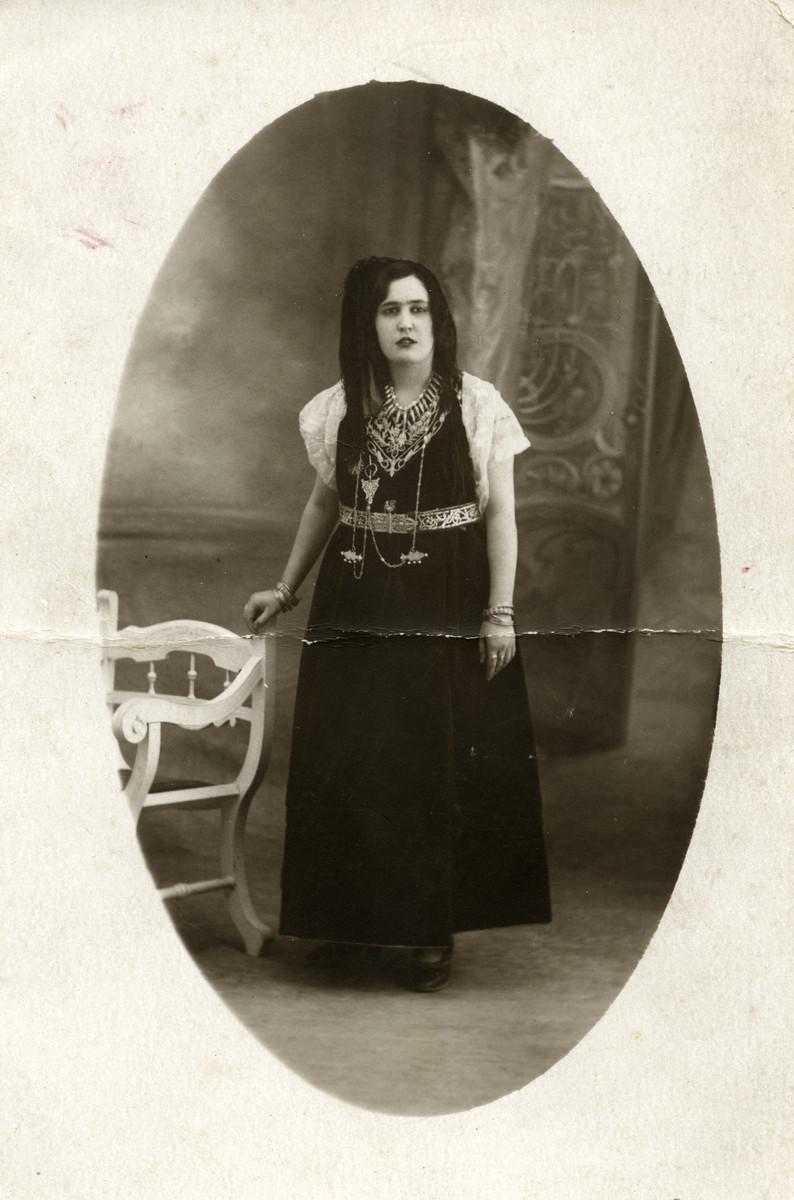 Close-up studio portrait of an Algerian Jewish woman wearing traditional garb.
