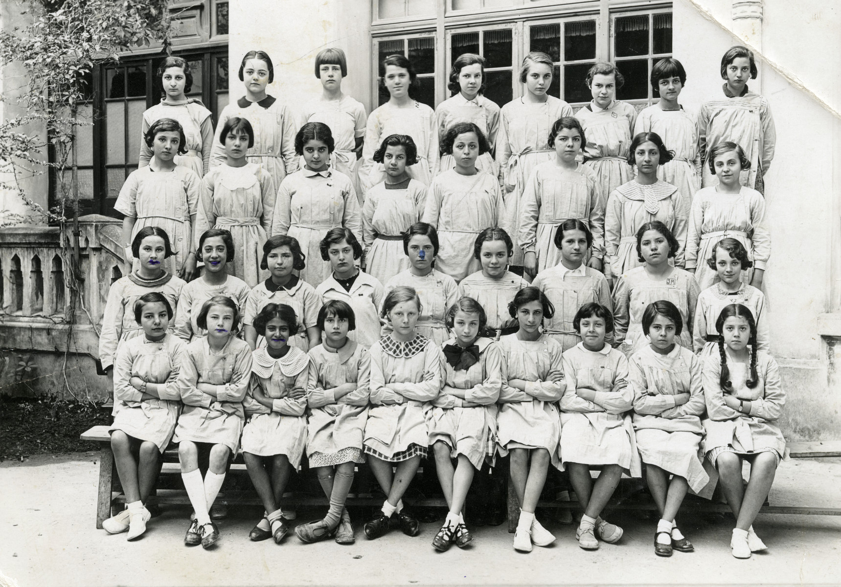 A group of Tunisian schoolgirls wearing aprons. Nadia Cohen is in the first row - 3rd from the left.