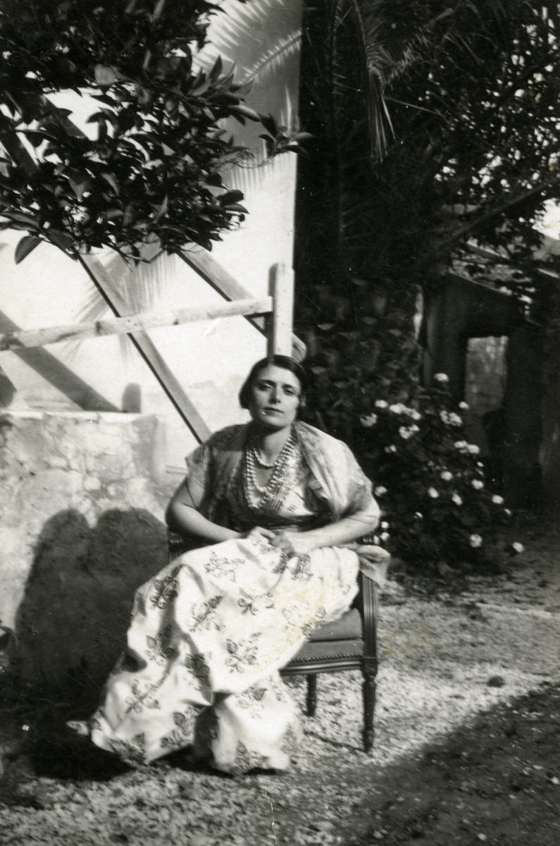 Terese Cohen sits in a garden wearing traditional dress.