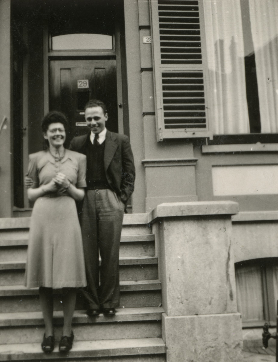 Femia van West and her fiance pose on the steps of a building.
