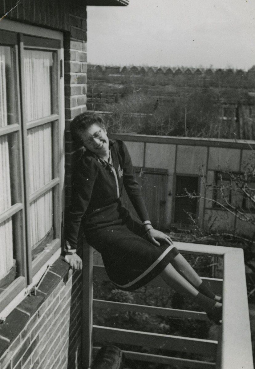 Femia van West perches on a ladder outside her home wearing a Star of David.