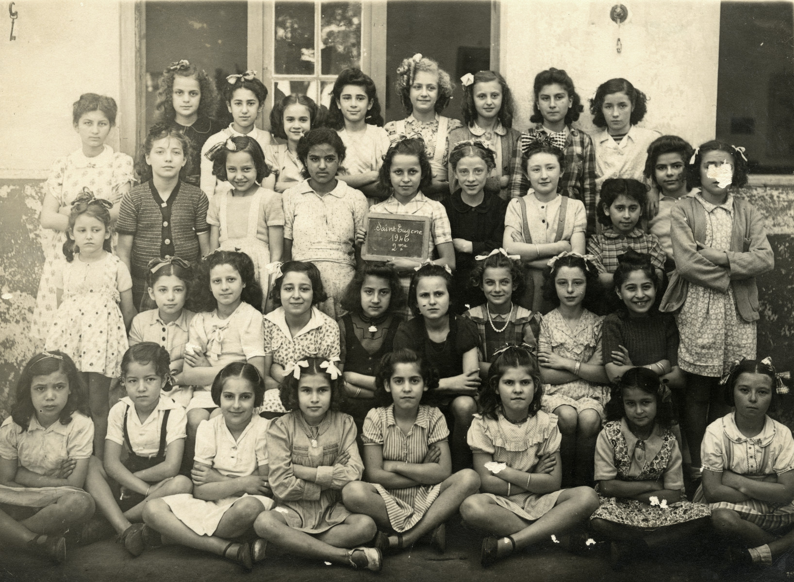 Class photo of young girls a school in Saint Eugene, Algeria.  Margalith Ghozlan is pictured as the first child in the second row.