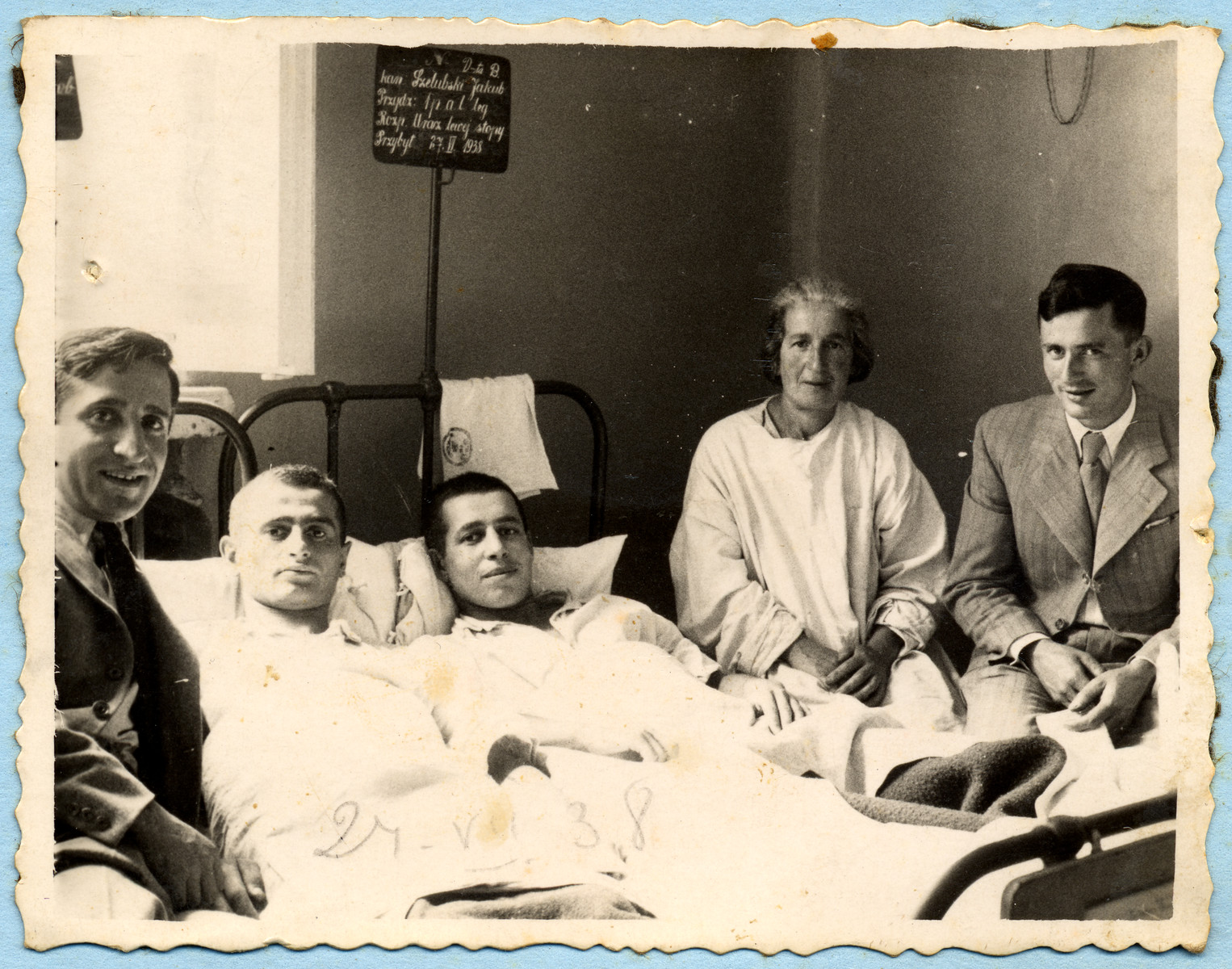 Two young men lie in a hospital bed in a hospital surrounded by family and friends.   Pictured lying on the right is Jan Szelubski, who was in hospital for a minor foot injury; next to him is his mother, Mirim Szelubski.