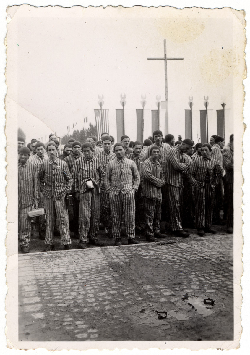 "Survivors, wearing their camp uniforms, stand in front of banners in the Buchenwald concentration camp.  Original caption reads ""Garb of inmates who survived"""