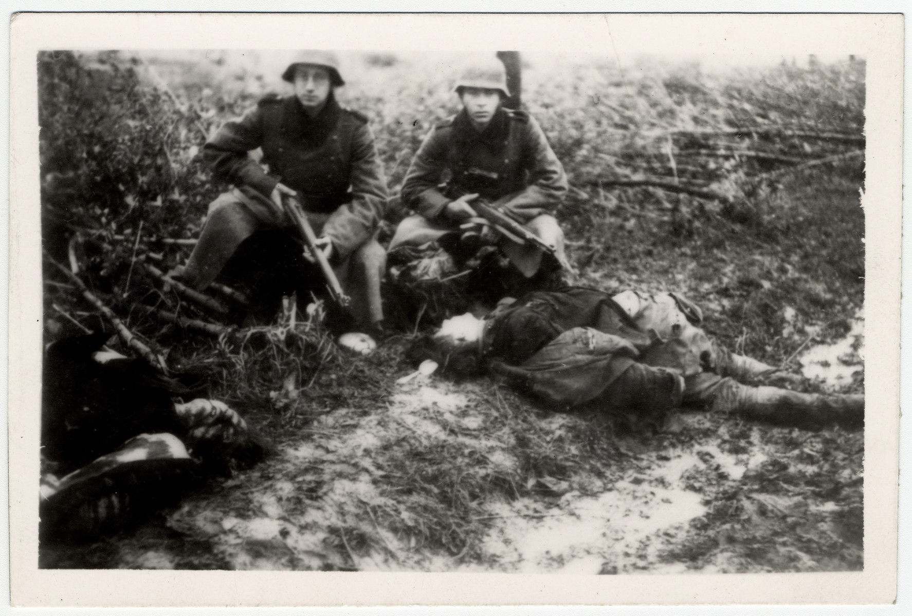 German soldiers pose with the corpses of two recently executed people.