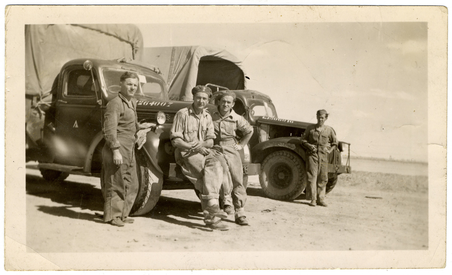 Four soldiers of the Polish Anders' Army, among them donor's cousin Mark Fruehman, are standing against army trucks in Egypt.