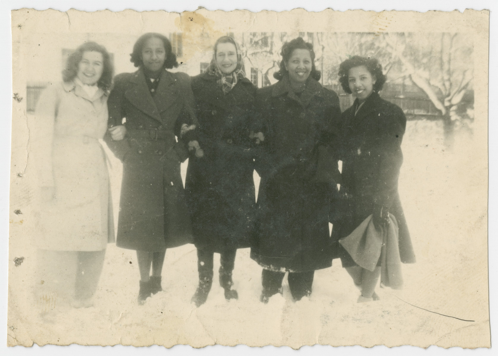 Five women stand in the snow on the grounds of the Liebenau internment camp.  Among those pictured are Ida, Marilyn and Jacqueline Johnson.
