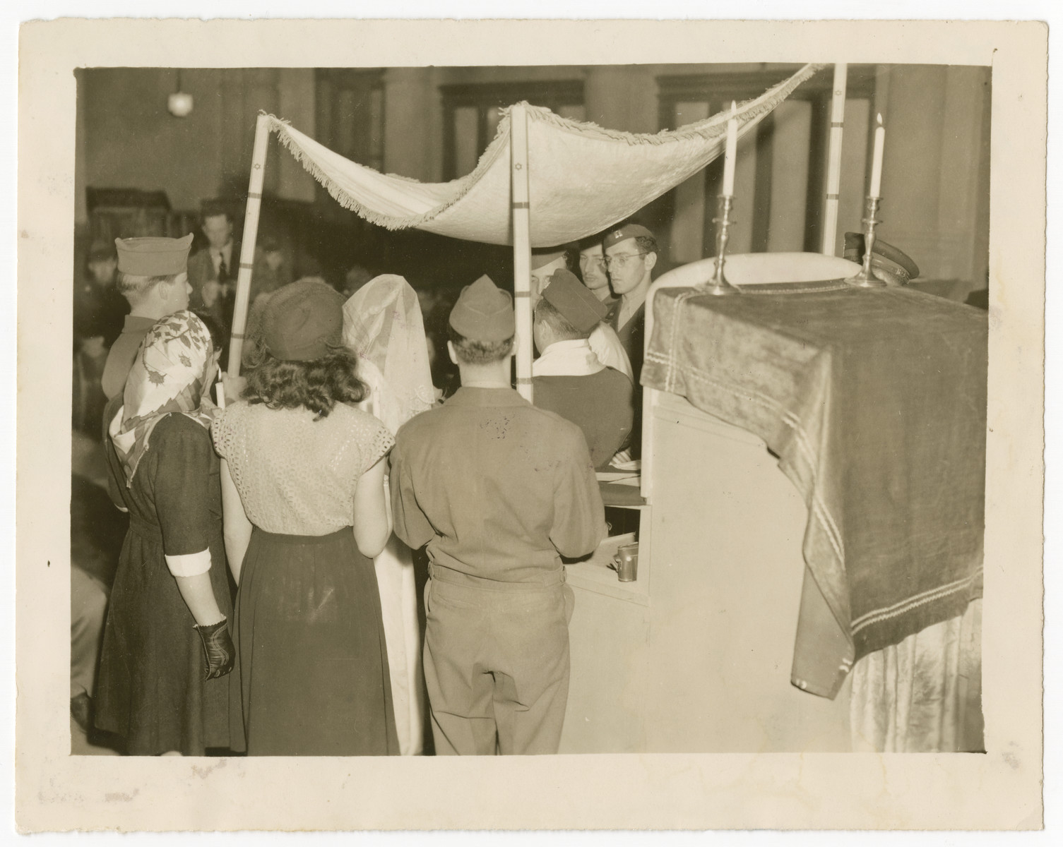 Rabbi William Dalin officiates at a wedding in the Zeilsheim displaced person camp.  Escorting the couple are American aid workers Lorna and Gil Adelman.