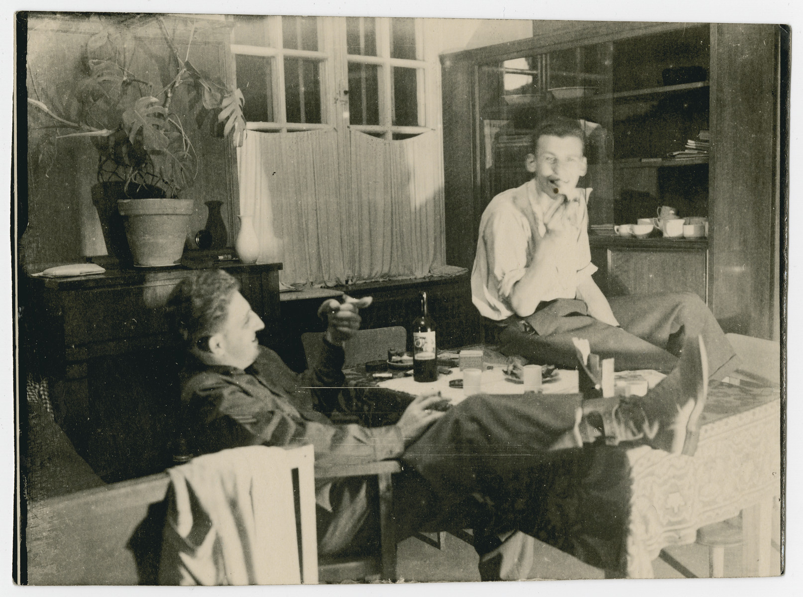 Norman Coulson relaxes in his quarters in the former Dachau concentration camp.    Seated on the right may be his assistant and former Polish prisoner Alfons.
