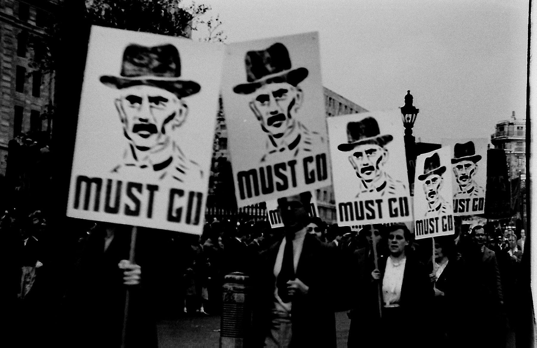 "Demonstrators march through London carrying signs with a portrait of Neville Chamberlain followed by the words ""Must Go"" [probably right after his signing of the Munich agreement]."