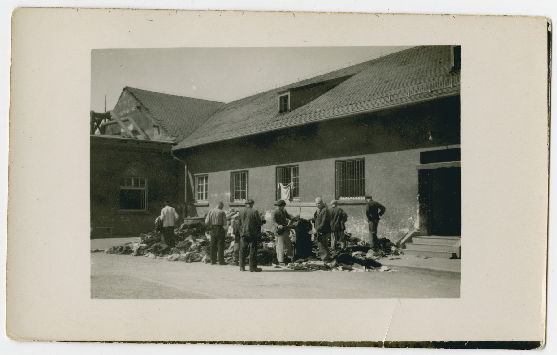 Survivors of the Dachau concentration camp sort through a pile of clothing outside a building following liberation.