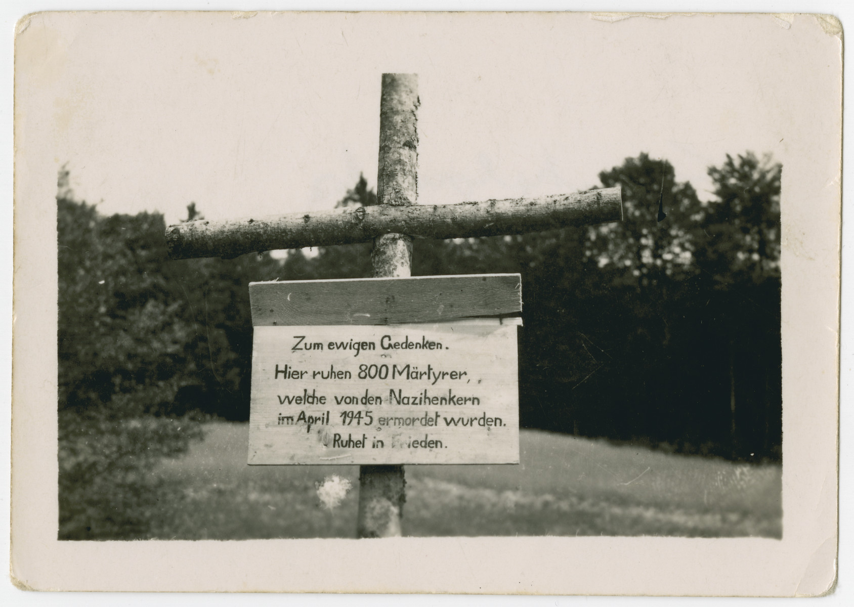 "A sign outside of the town of Nammering marks the site of a mass shooting by the SS.  It reads:  ""In eternal memory.  Here lie 800 martyrs who were murdered by Nazi executioners in April 1945.  May they rest in peace."""
