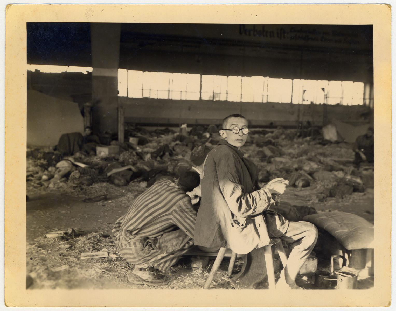 A survivor sits on a stool inside a barrack in Nordhausen surrounded by corpses.