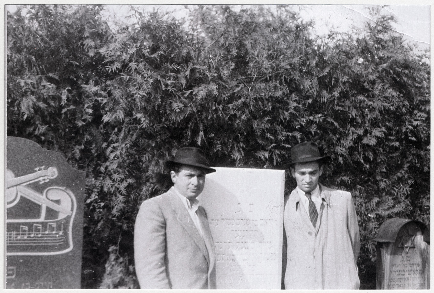 David Klinger pictured (on right) with his cousin Motek Weingarten pose by the tombstone of Joel Klinger.