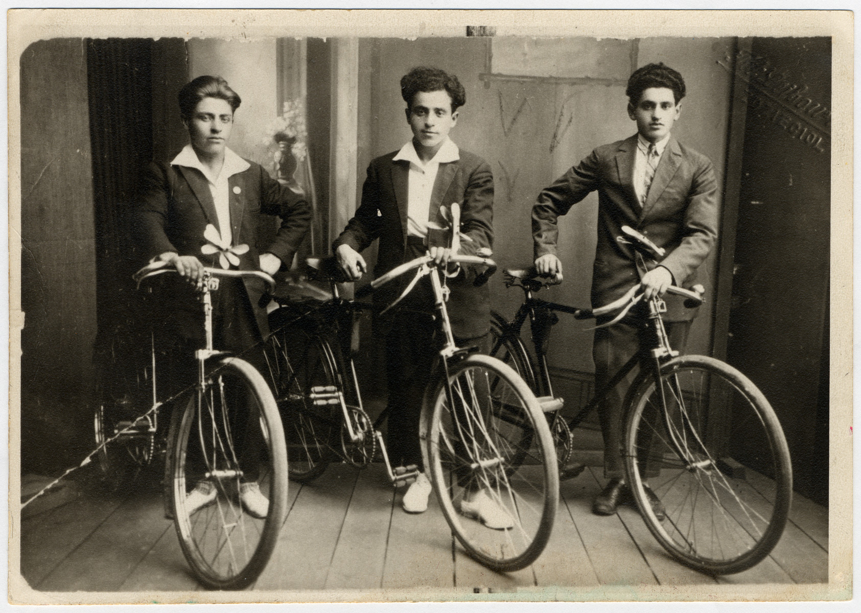 Studio portrait of three young men with their bicycles.  Shlamke Minuskin is pictured at the left.