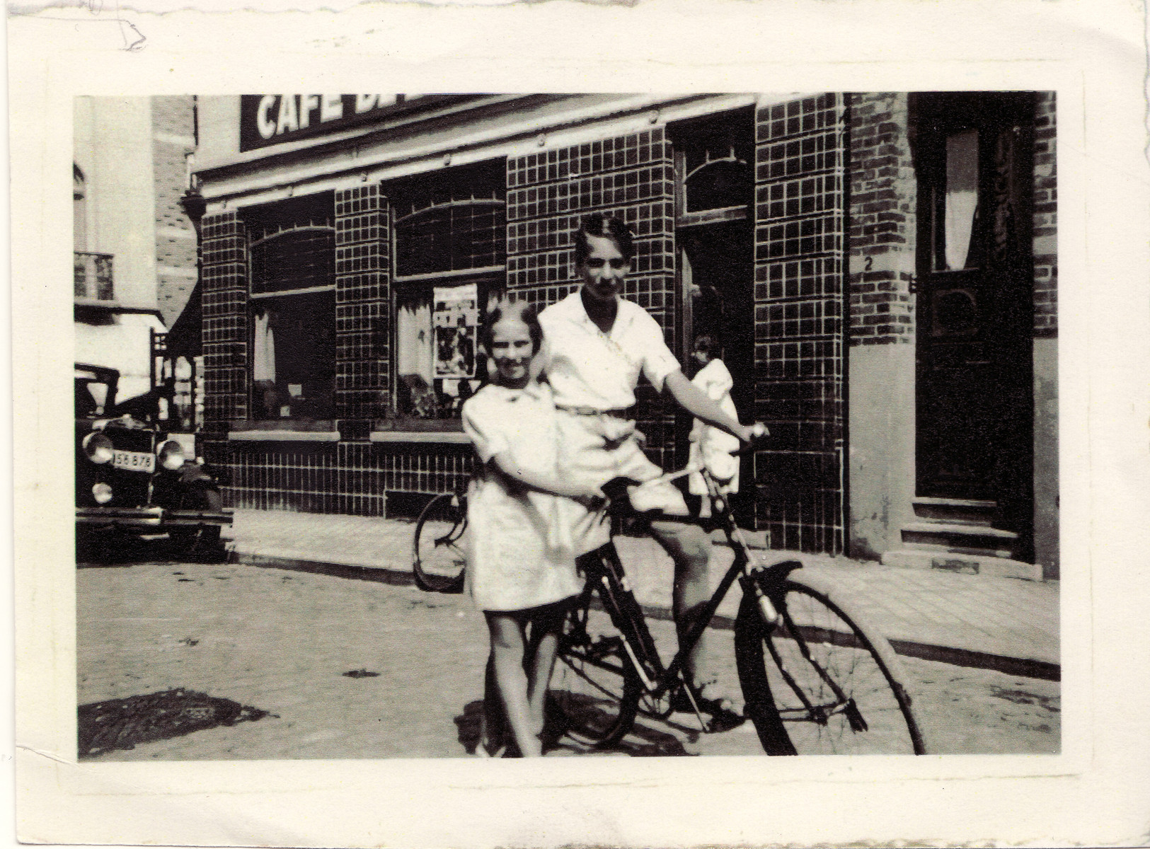 Eva and Heinz Geiringer pose with a bicycle on a street in Belgium after fleeing Vienna.