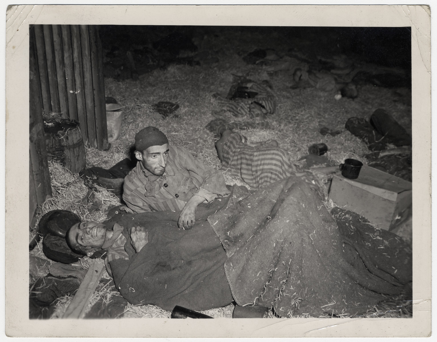 Two survivors lie down on the straw inside a barrack in Nordhausen.