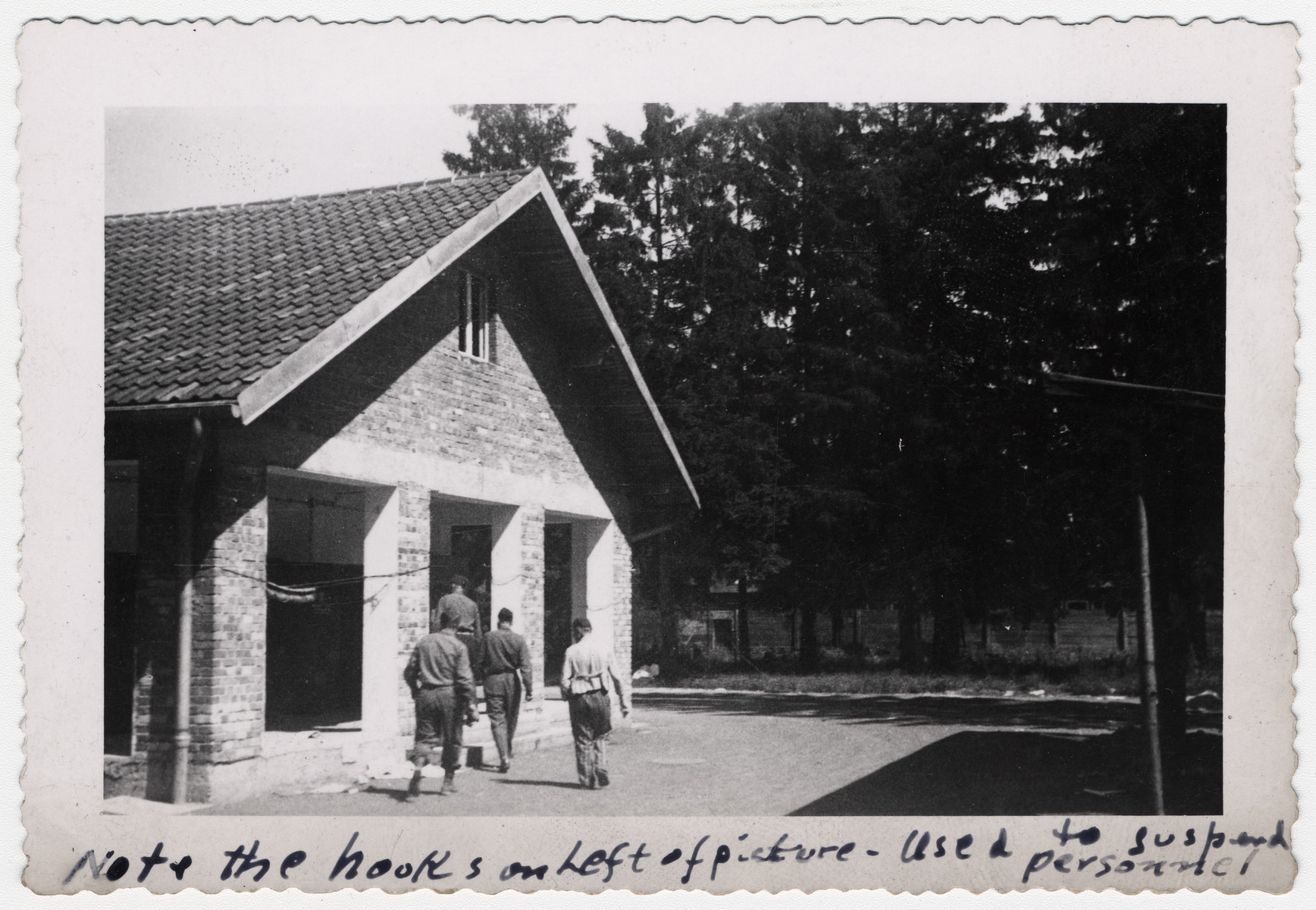 "American soldiers inspect a building in the Dachau concentration camp that had been used for torture.  The original caption reads: ""Note the hooks on the left of picture -- Used to suspend personnel""."